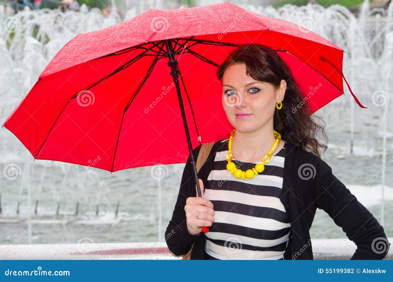 Flickan med ett paraply på springbrunnen