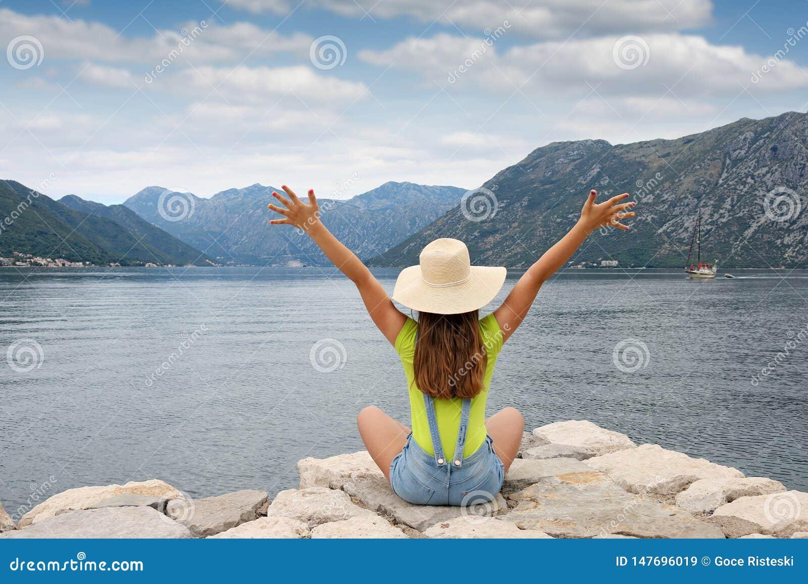 Flickan med händer tycker om upp en Kotor för sommarferie fjärd