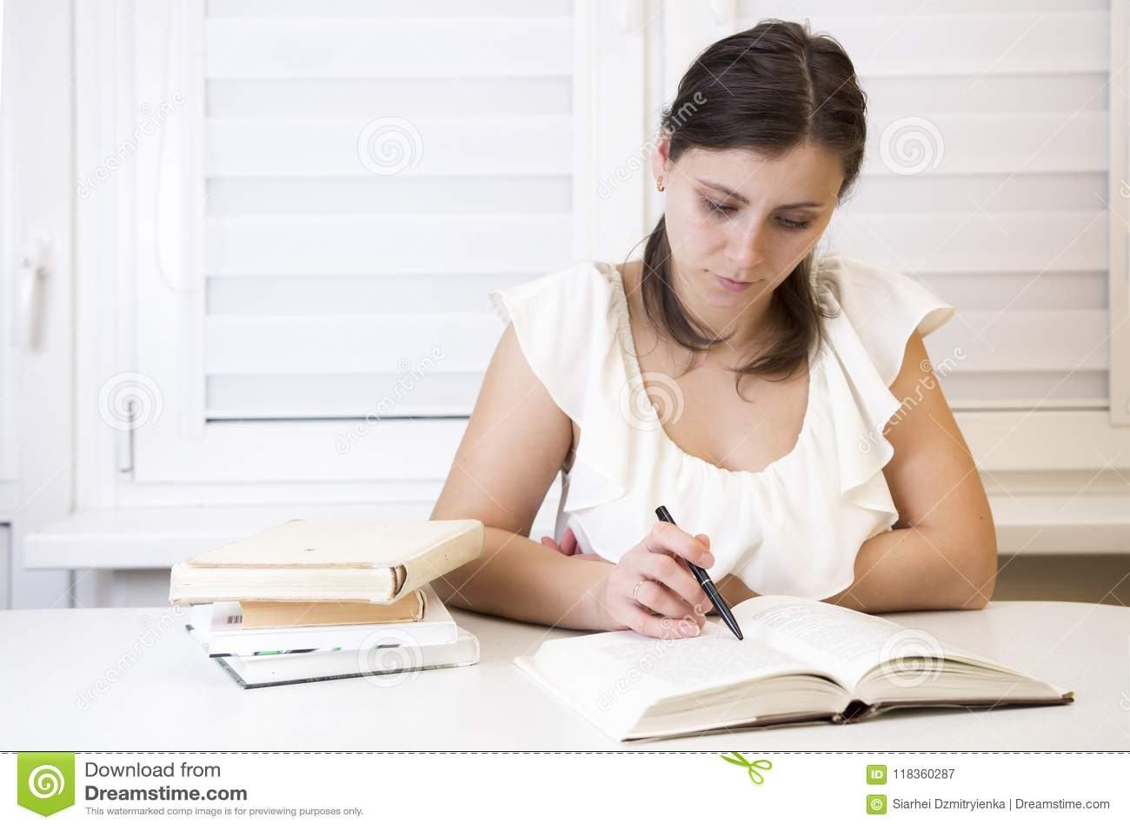 Flickan med läroböcker förbereder sig för undersökningar på universitetet Den unga brunetten undervisar kurser Kvinna på perioden