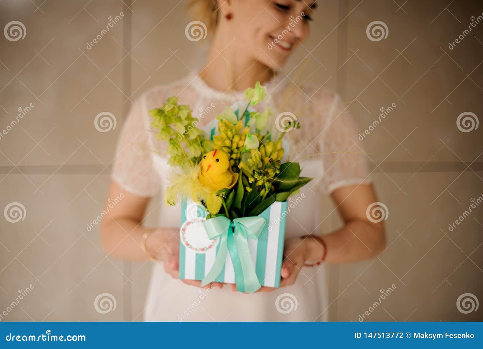 Flickan rymmer den randiga hattasken med blommor och leenden