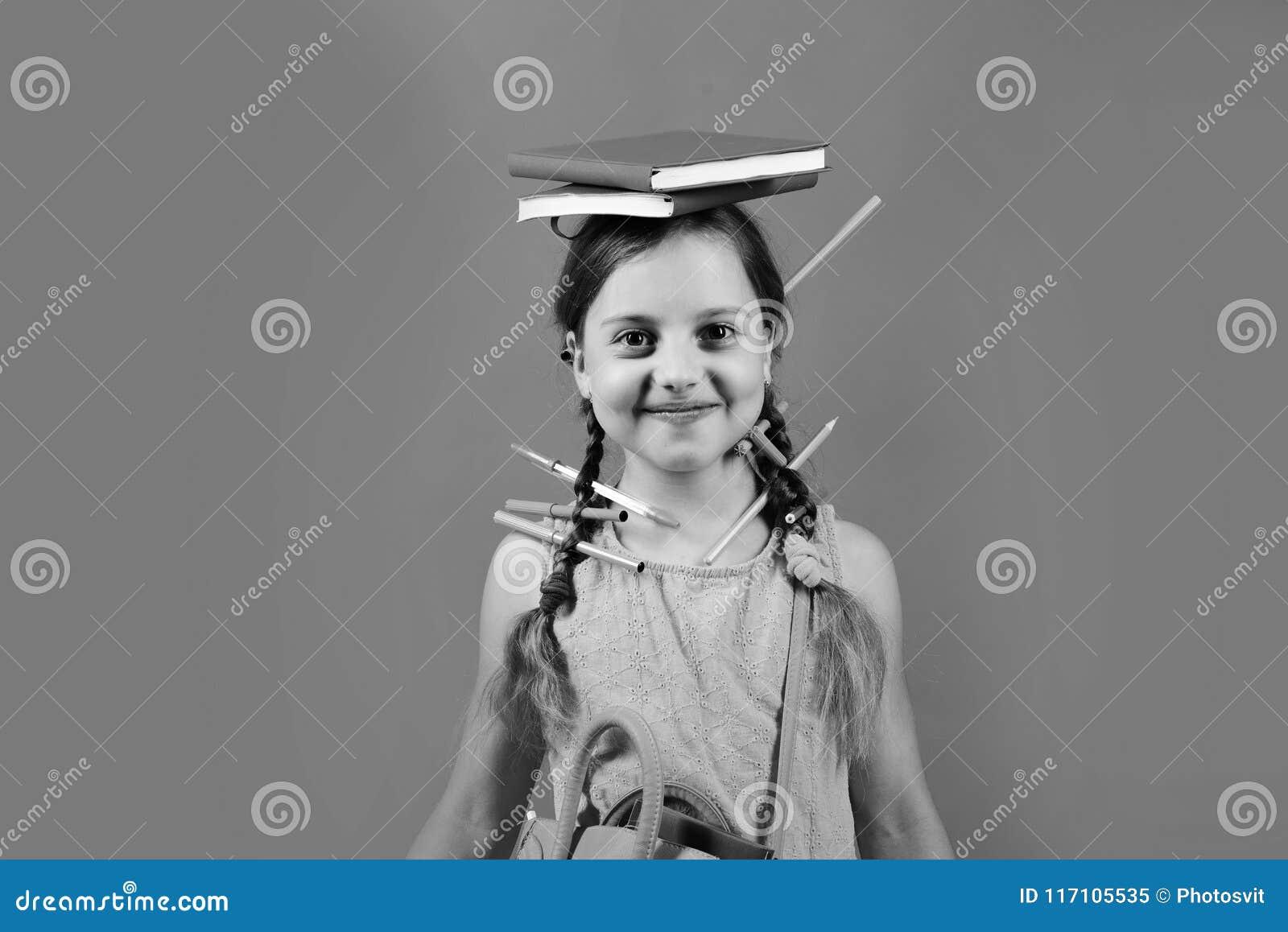 Flickan rymmer röda och blåa böcker på huvudet