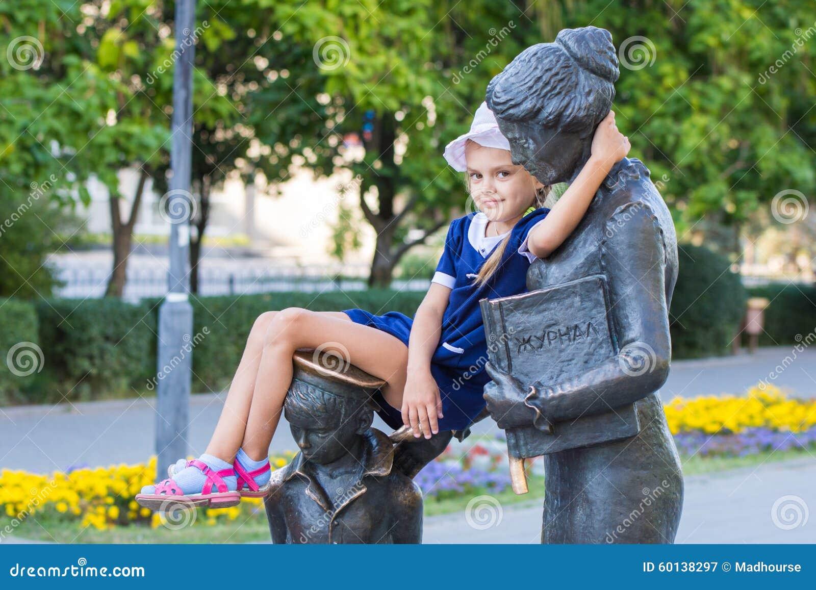 Flickan satt bekvämt på monumentet till den första läraren