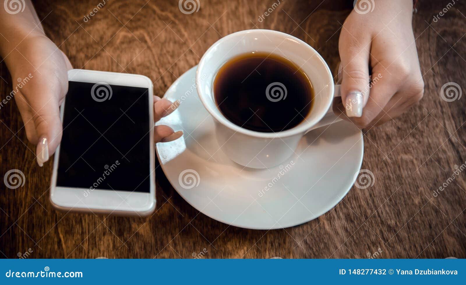 Flickan sitter i ett kaf? och rymmer en kopp te och en telefon i hennes h?nder som v?ntar p? en appell