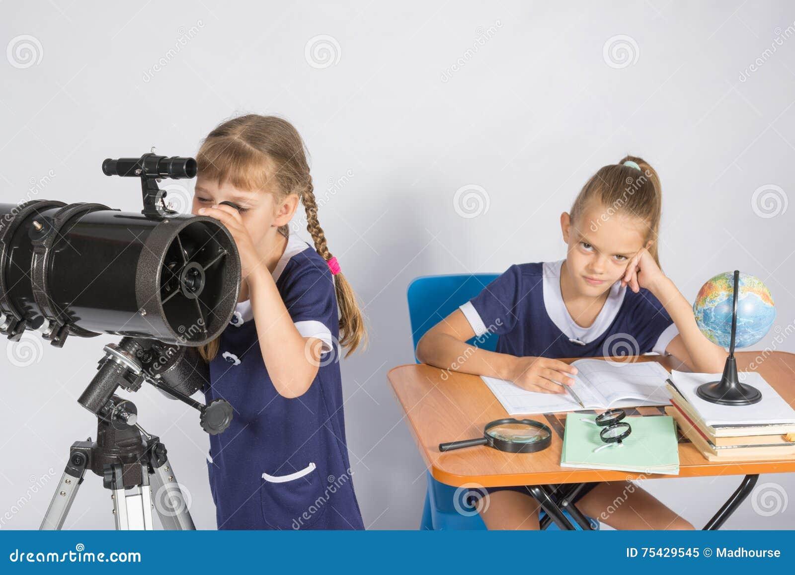 Flickan som astronomen ser himlen till och med ett teleskop, den annan flickan, sitter på tabellen