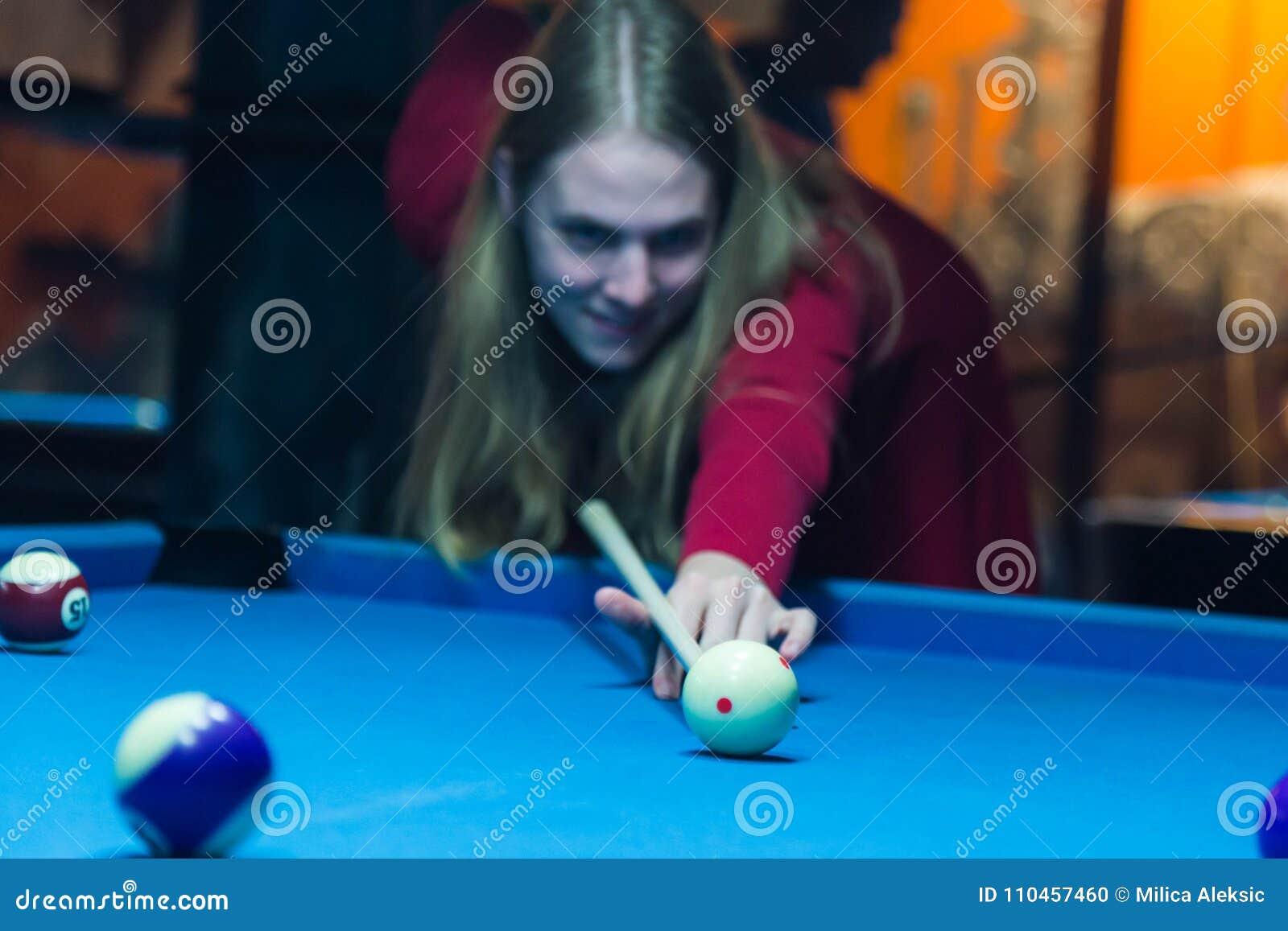 Flickan spelar en billiard på klubban