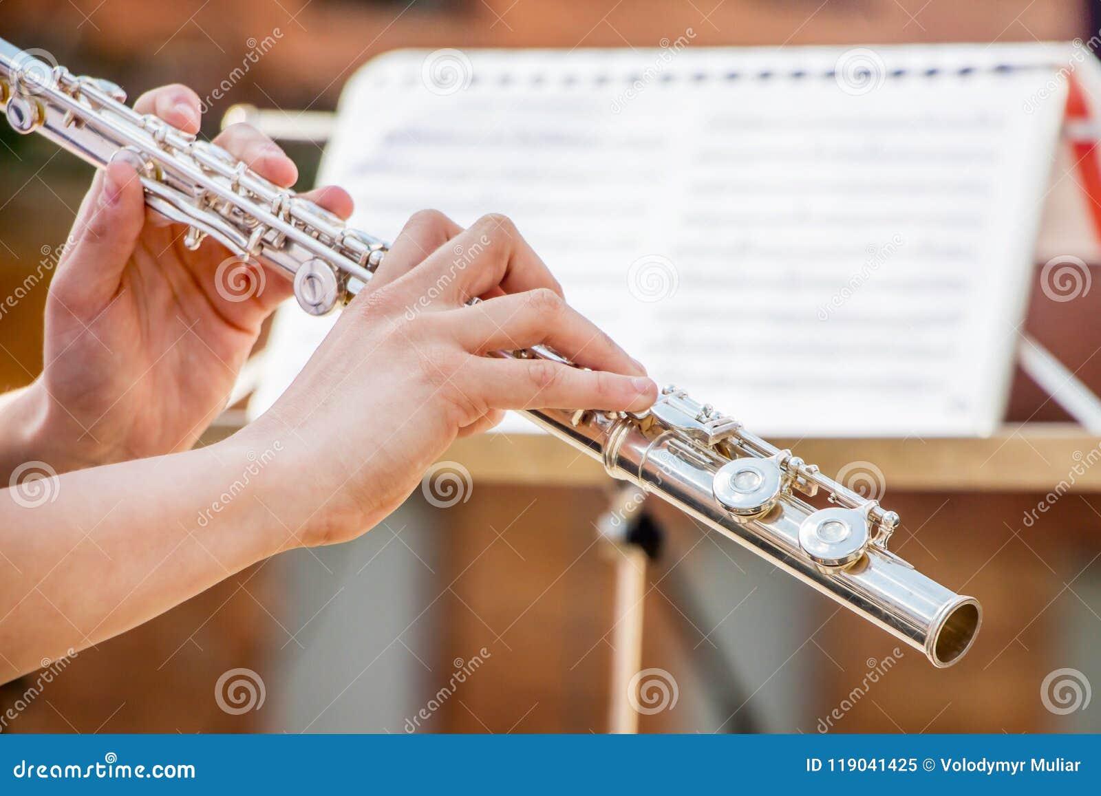 Flickan spelar flöjten Blåsa flöjt i händerna av musikerduren