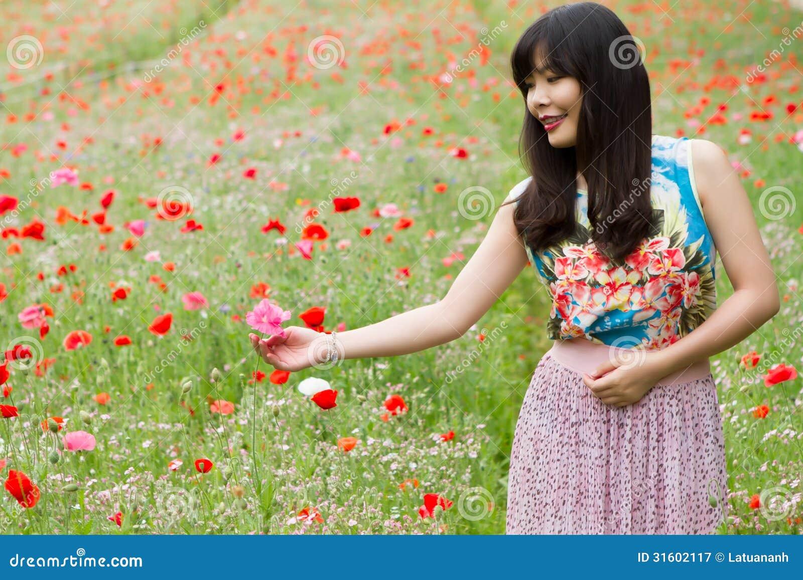 Flickan spelar med en blomma i vallmofält