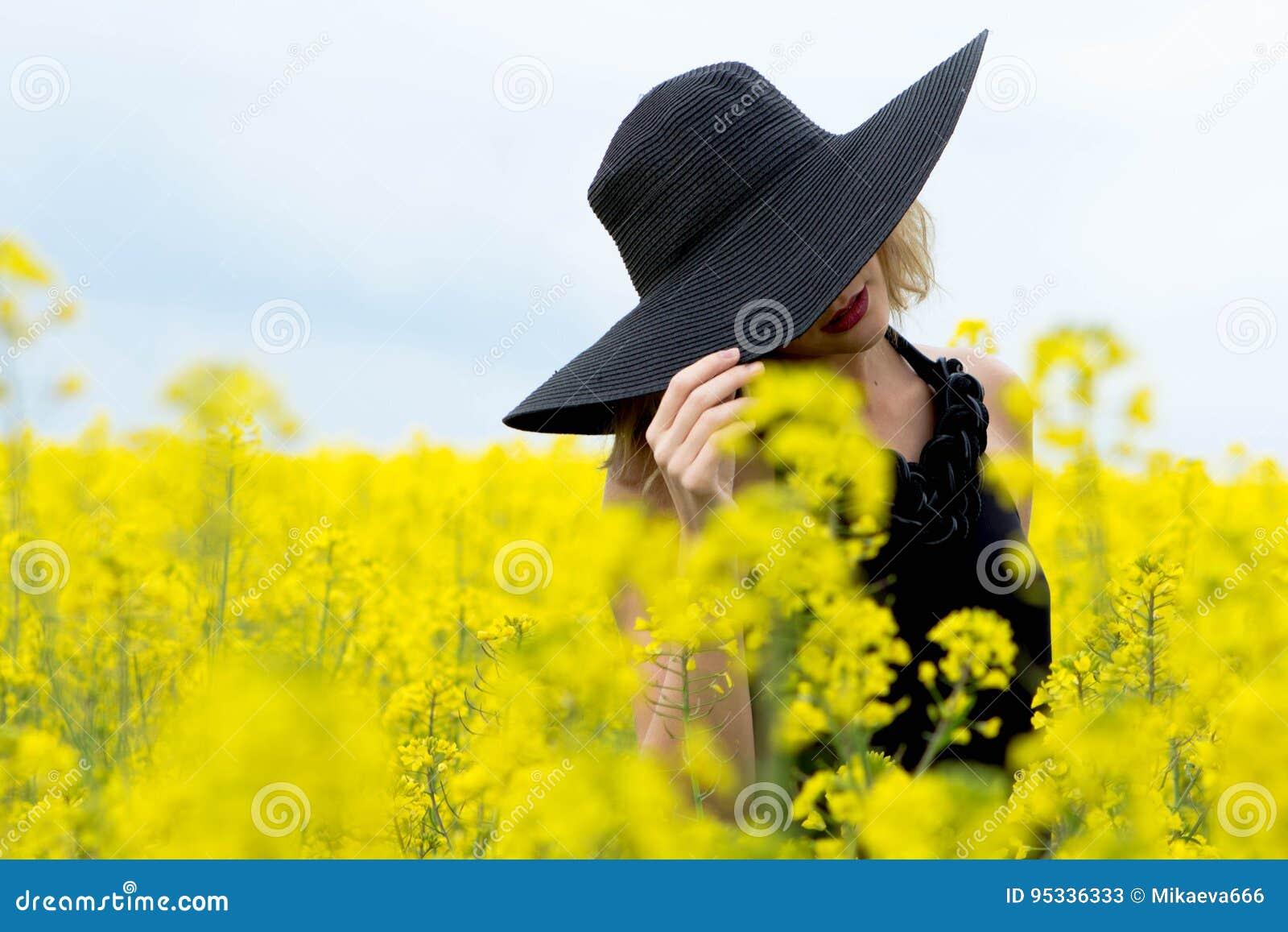Flickan täckte hennes framsida med en hatt i fältet med blommor