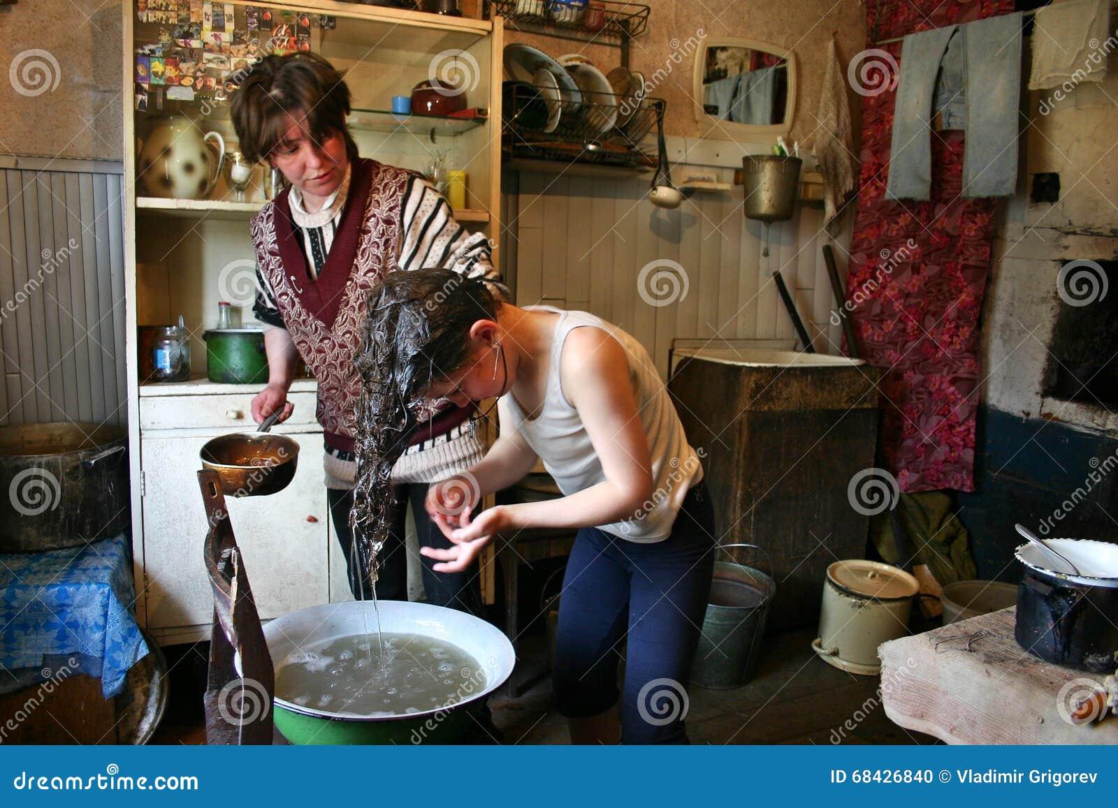 Handfat lantligt : Flickan tvättar hennes huvud i en emaljhandfat det lantliga huset