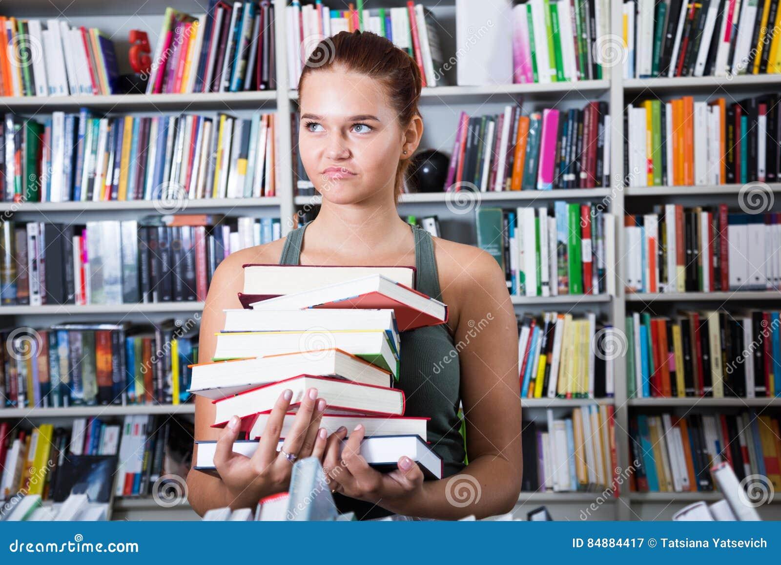 Flickan väljer en bok i universitetarkiv