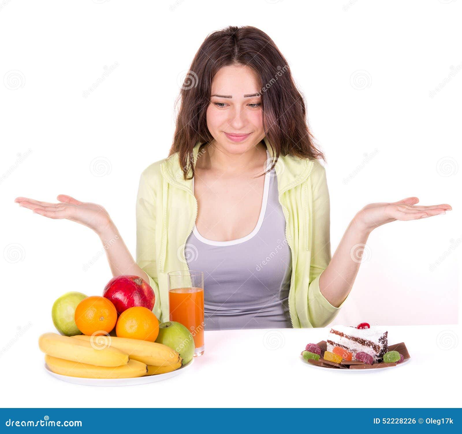 Flickan väljer mellan frukt och sötsaker