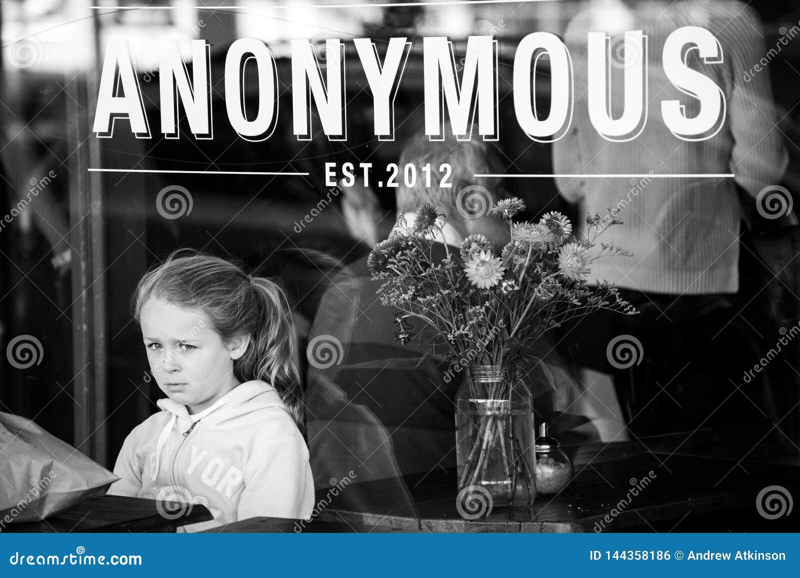 Flickan väntar på beställning bara på ett kafé som ser ledset och bara