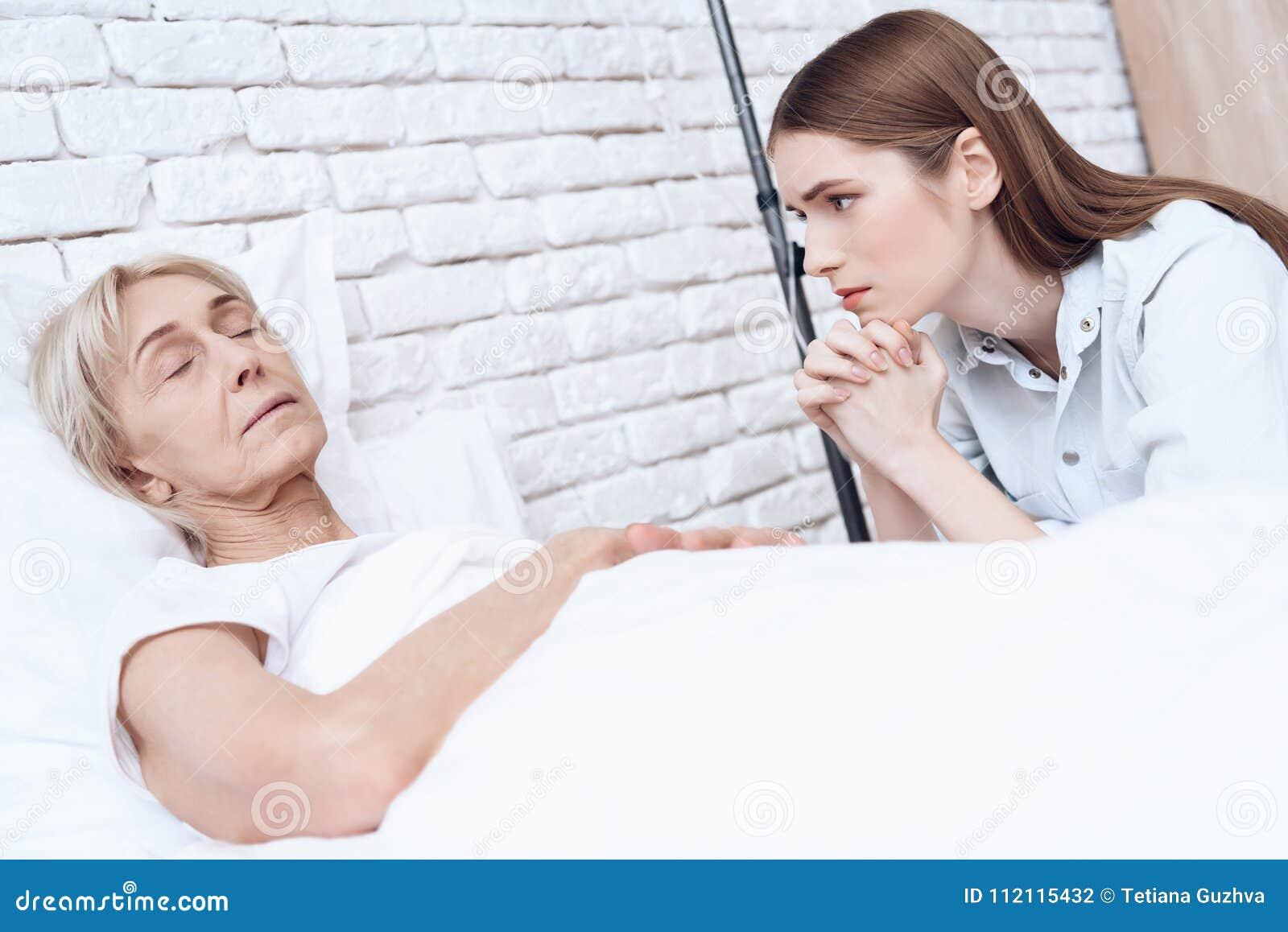 Flickan vårdar den äldre kvinnan hemma Kvinnan känner sig dålig, flickan oroas om henne