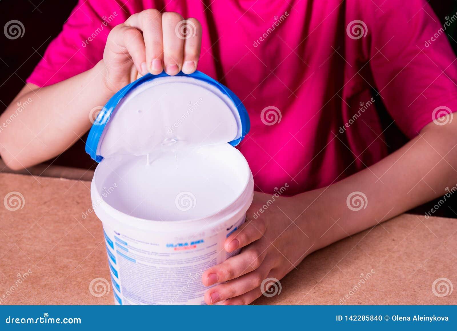 Flickans hand öppnar kan av vit akrylmålarfärg