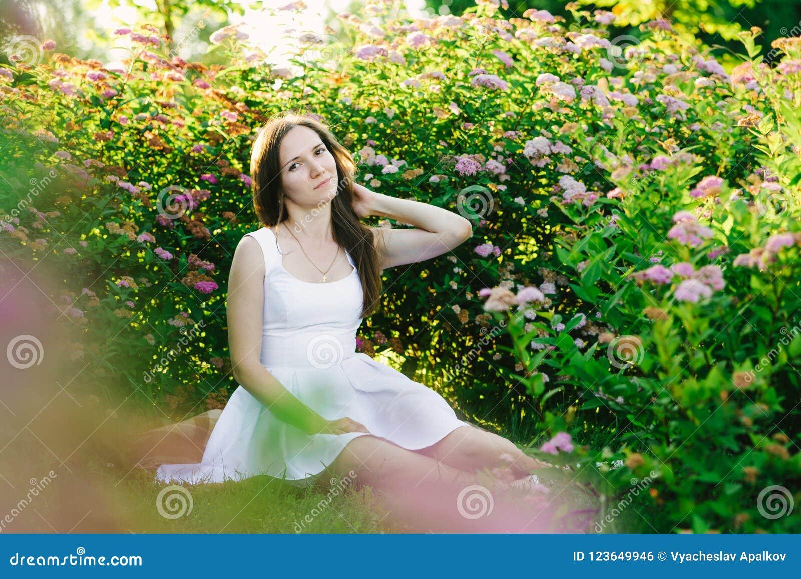 Flickasammanträde i en buske av rosa blommor