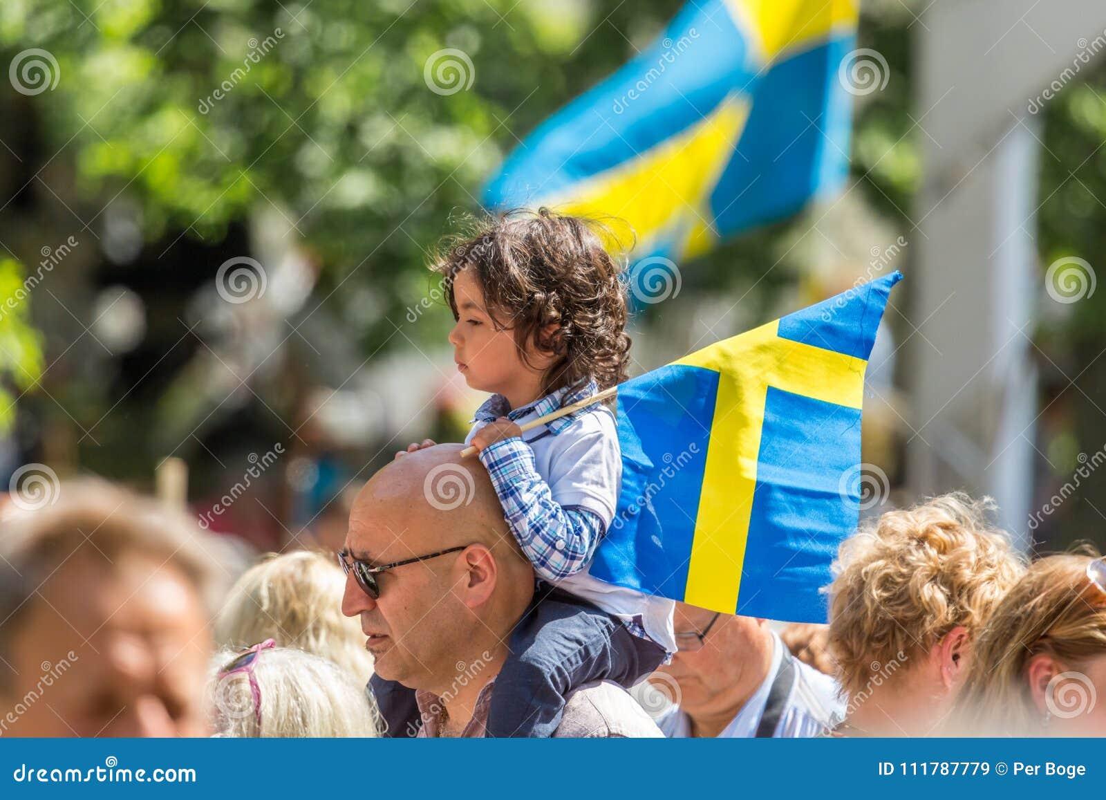 Flickasammanträde på a mans skuldran som rymmer en svensk flagga