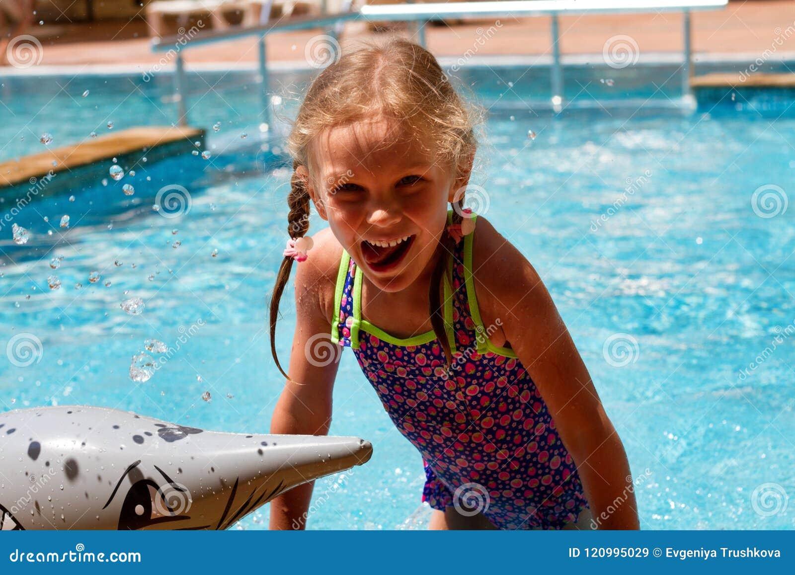 Flickasimning i en pöl som ler och har en lycklig dag