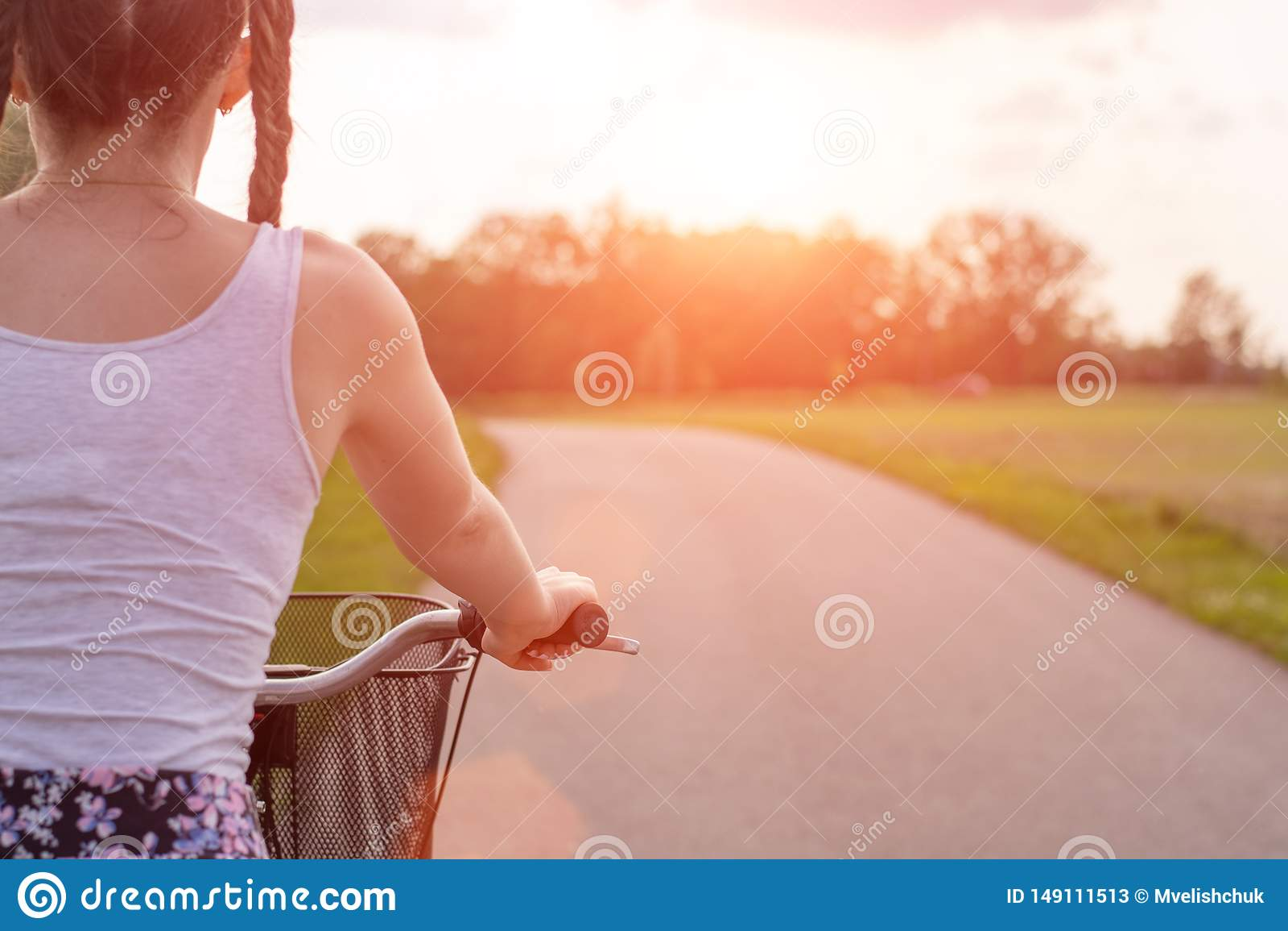 Flickaslutet med cykeln p? sommarsolnedg?ngen p? v?gen i staden parkerar upp Cykla ner gatan som arbetar p? sommarsolnedg?ngen