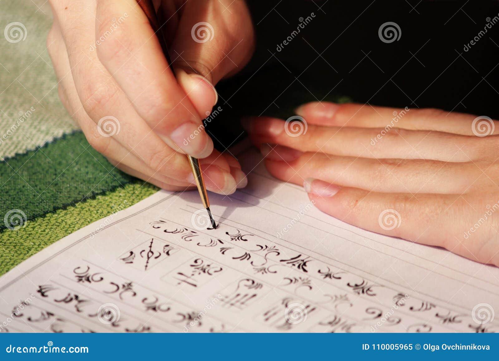 Flickastudenten lär att dra monogram för att dra dem på spikar, när han skapar en manikyr med färgschellack akryl svart p