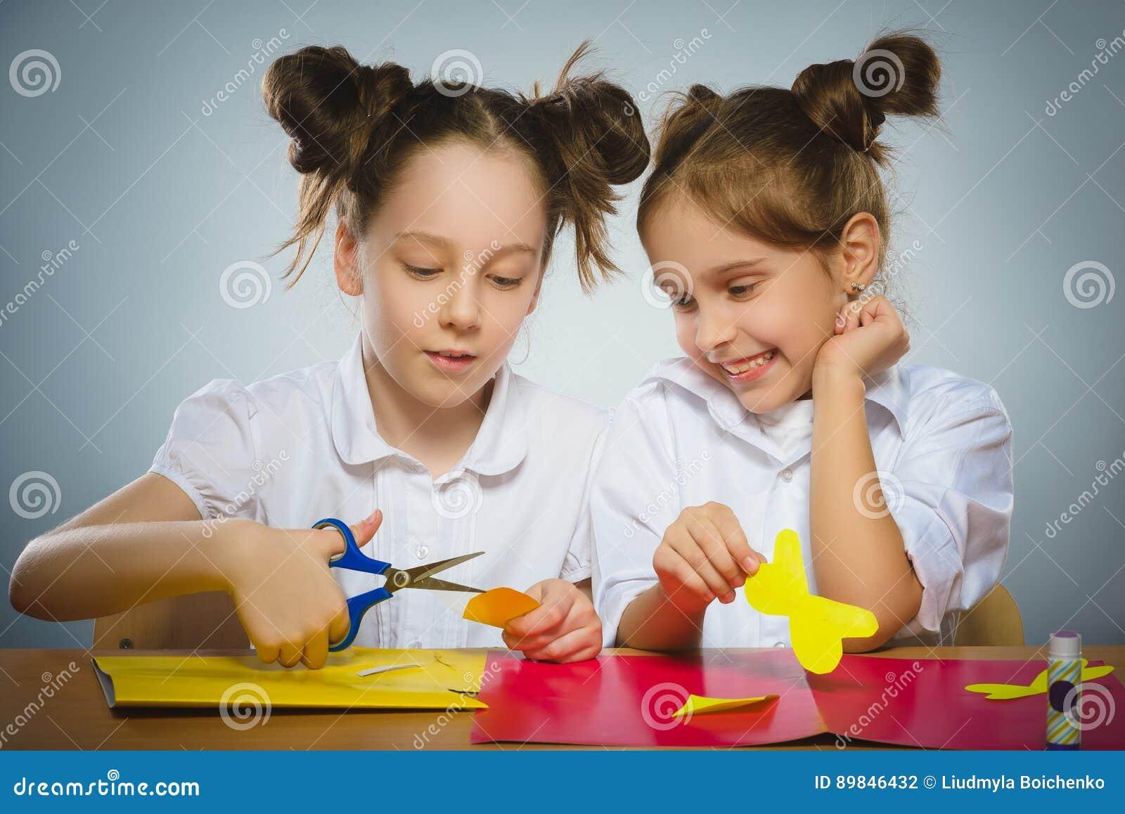 Flickor gör något från kulört pappers- användande lim och sax