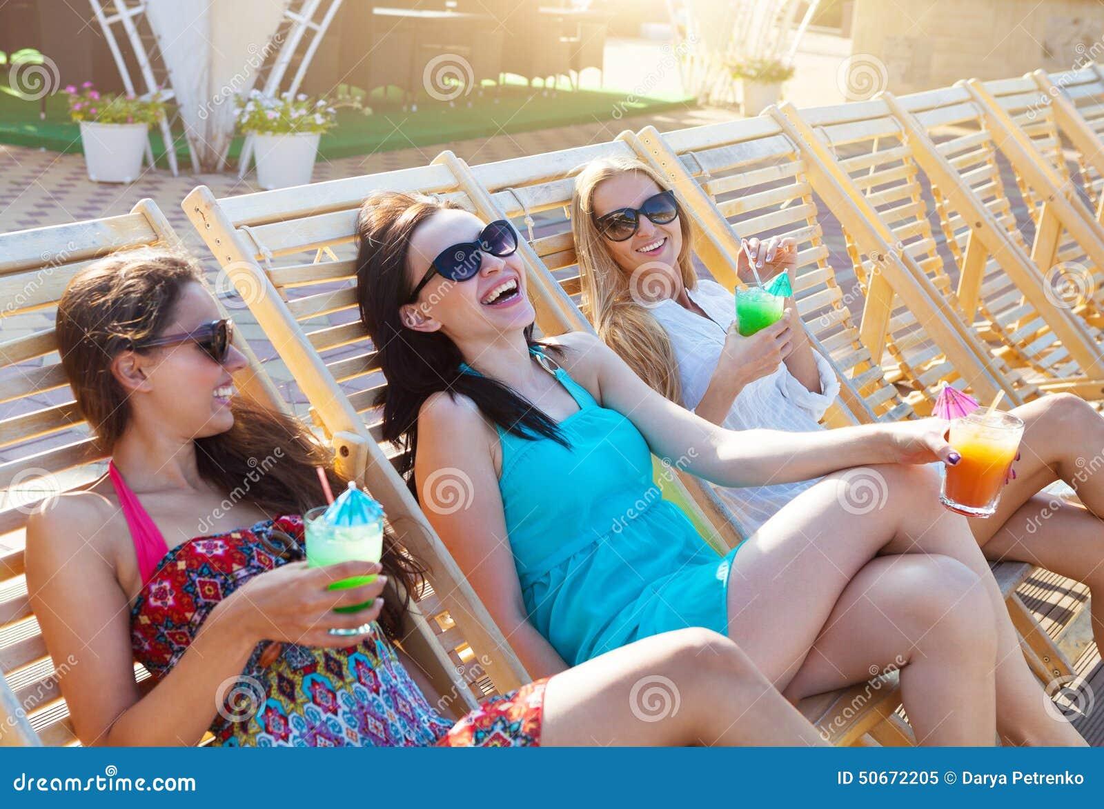 Flickor med drycker på sommar festar nära pölen