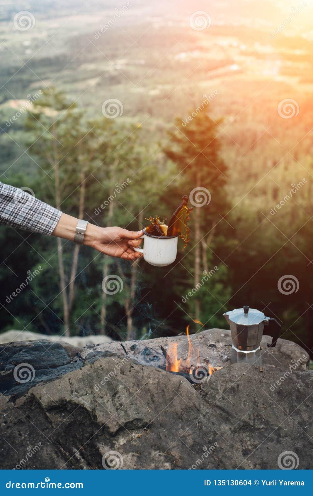 Flickor räcker rymmer en varm kopp kaffe nära lägerelden på bakgrund av naturen under solnedgången