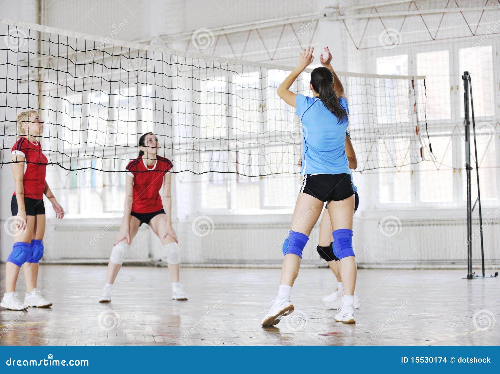 Flickor som leker för volleyboll leken inomhus