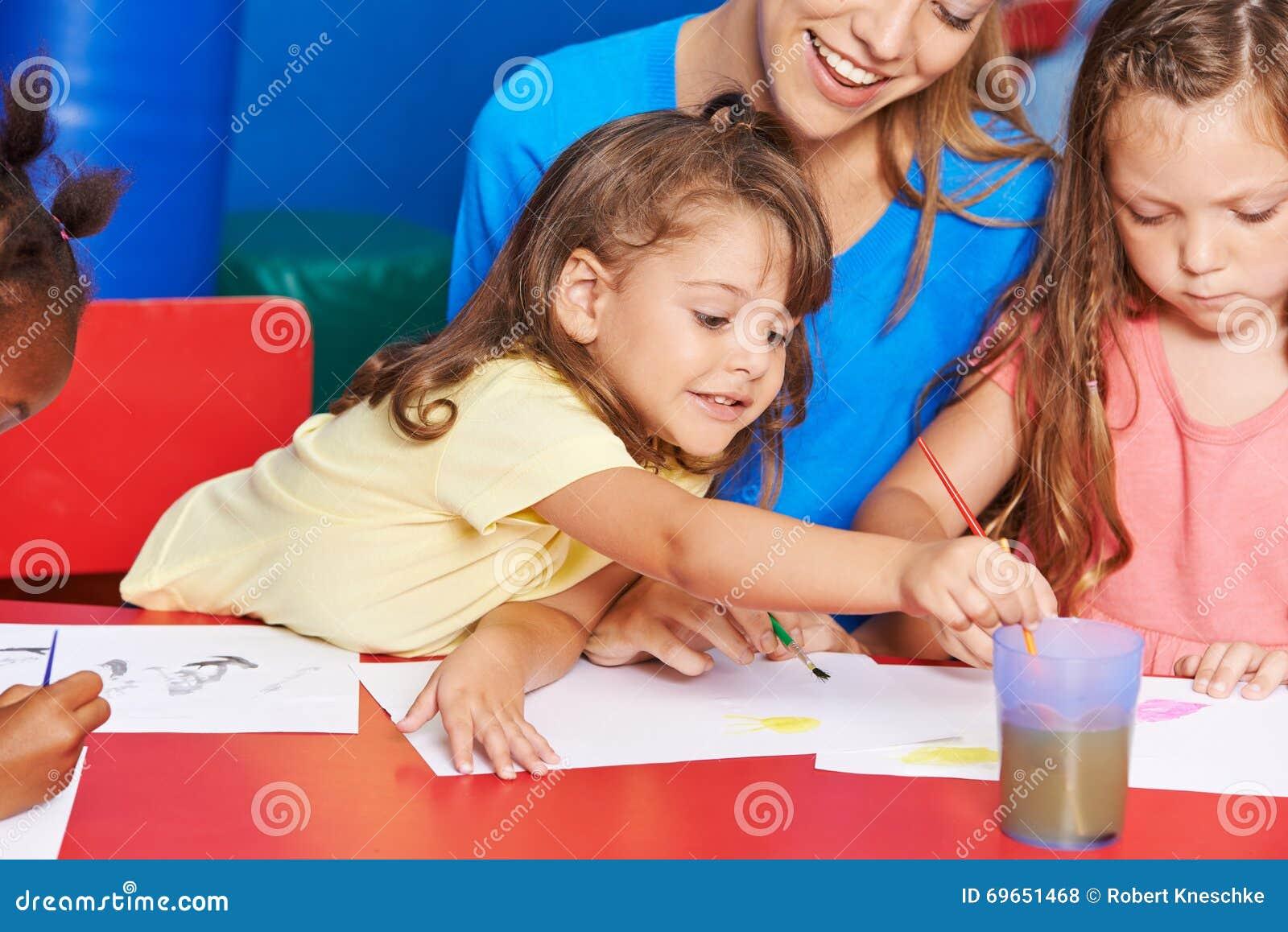 Flickor som målar i konstgrupp i grundskola