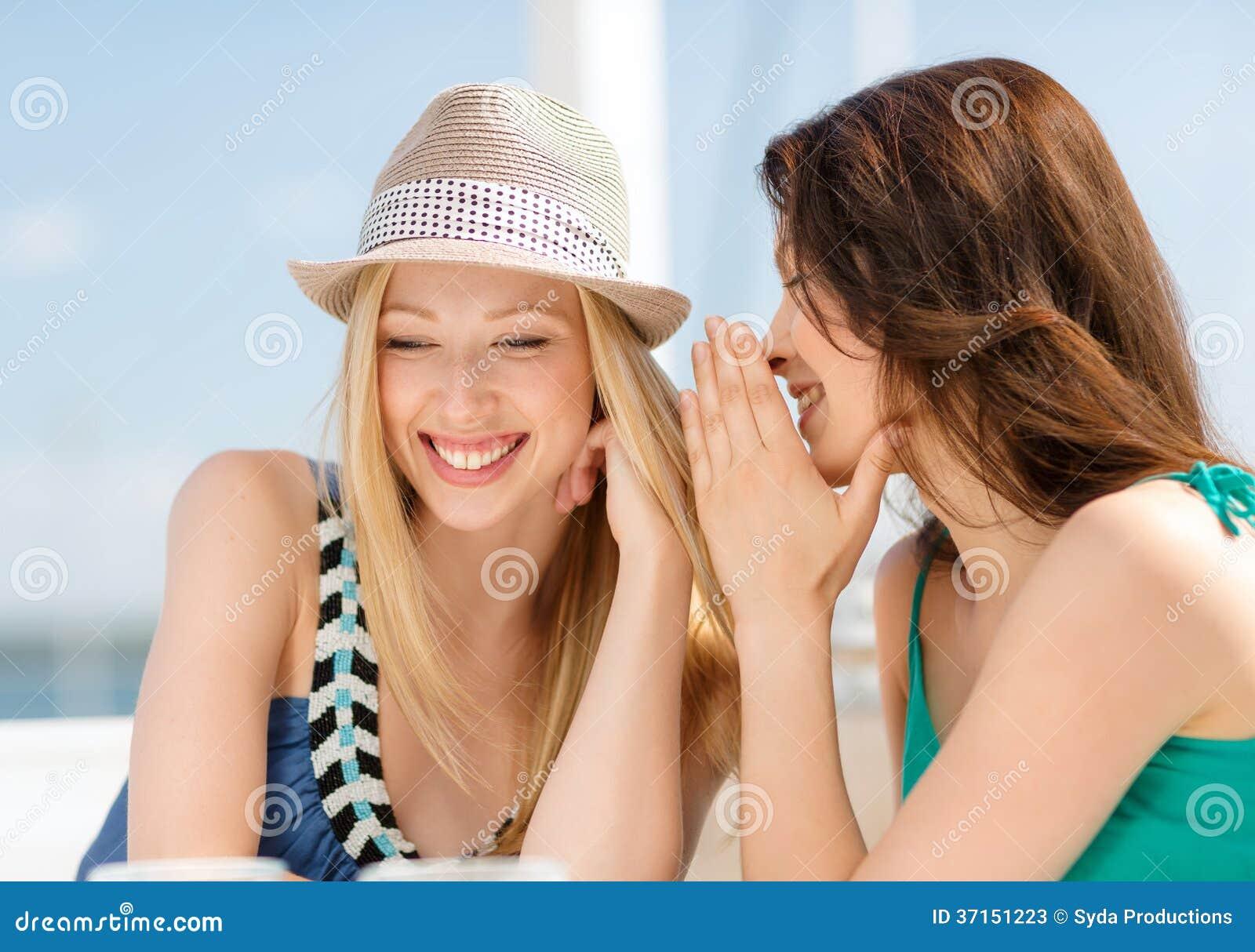 Flickor som skvallrar i kafé på stranden