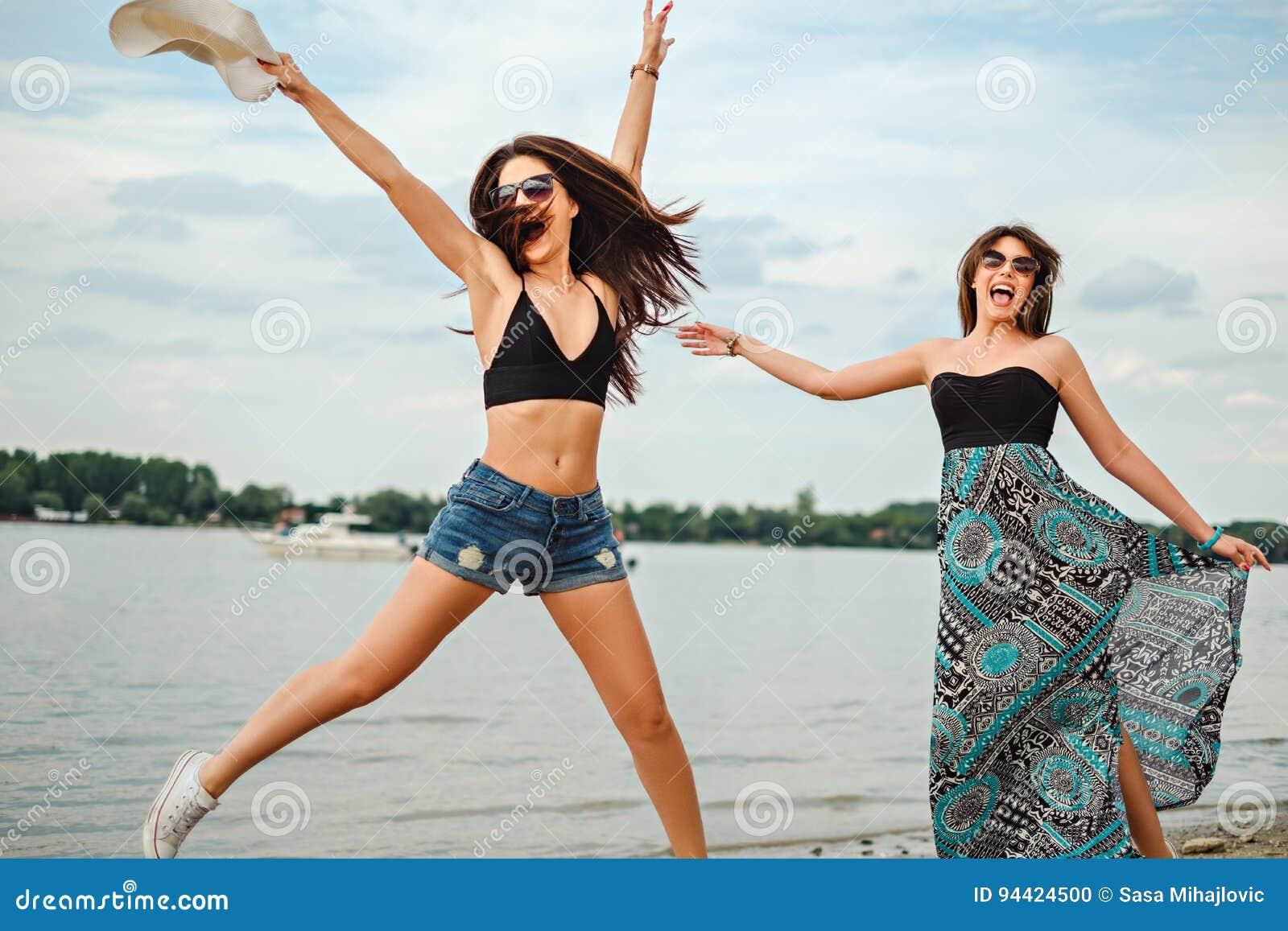 Flickvänner som hoppar på stranden