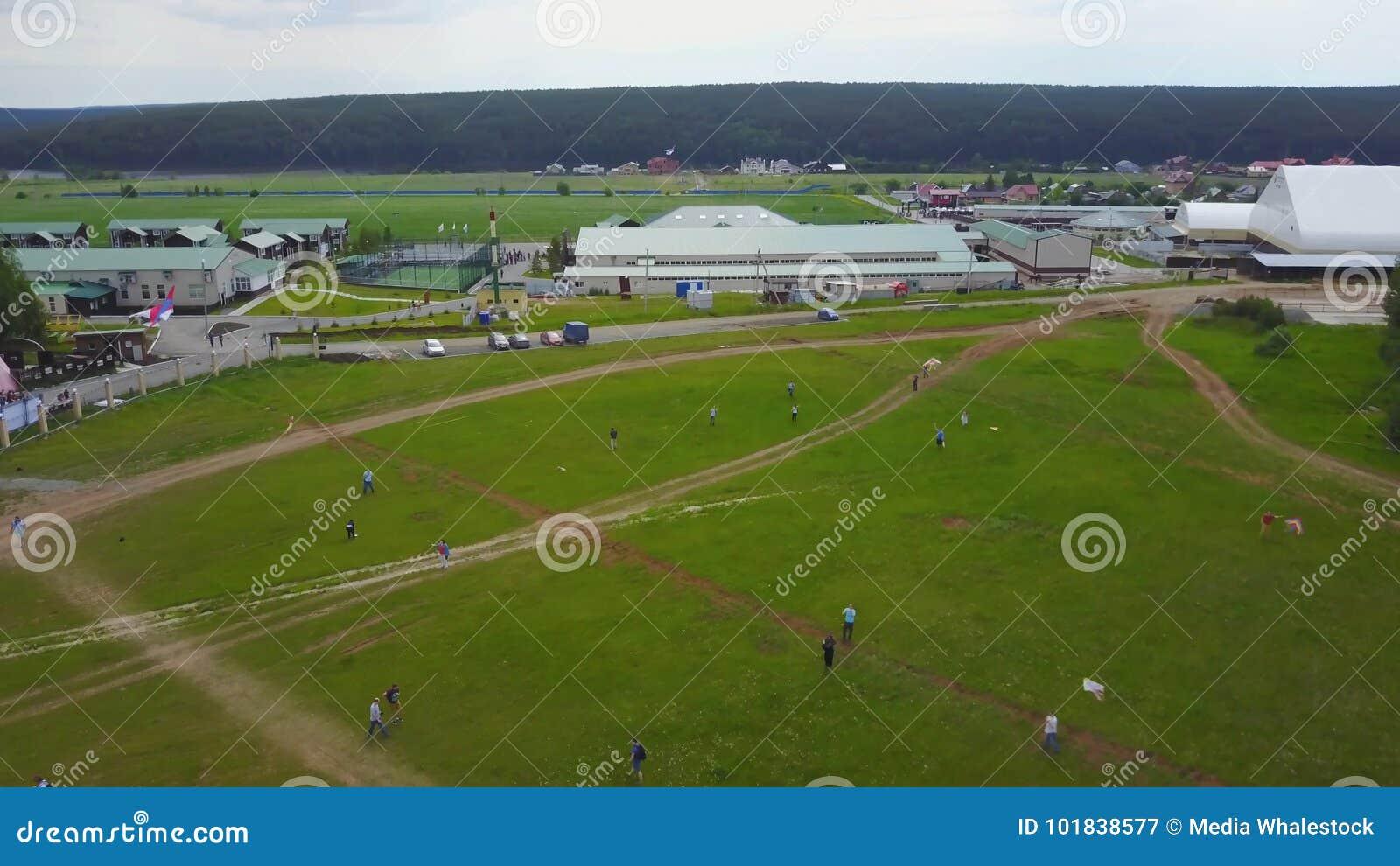 Flie de personnes un cerf-volant sur l herbe dans le jour d été Enfants de groupe pilotant le cerf-volant extérieur Cerf-volant d