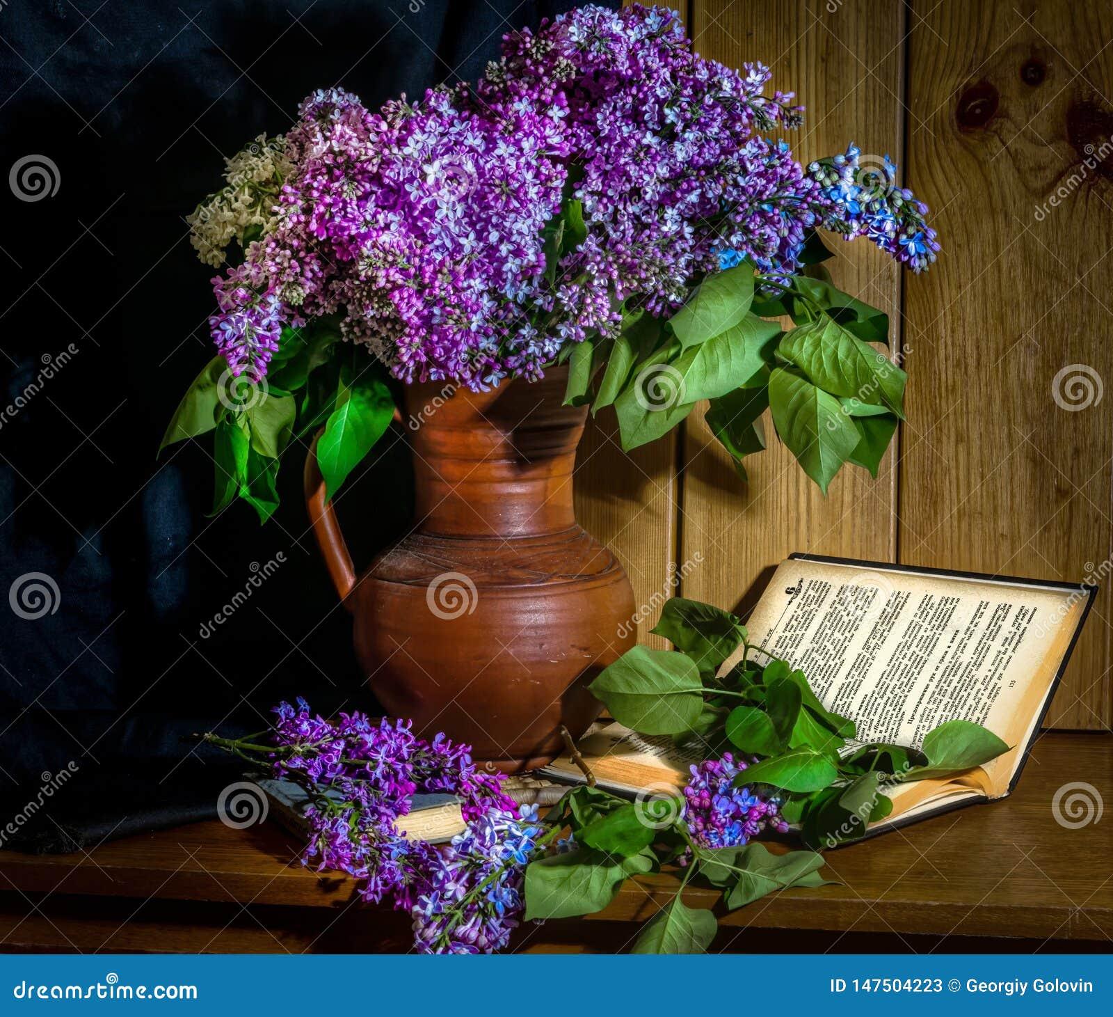 Flieder in einem keramischen Vase, in einem Buch und in einer Stunde auf dem Tisch
