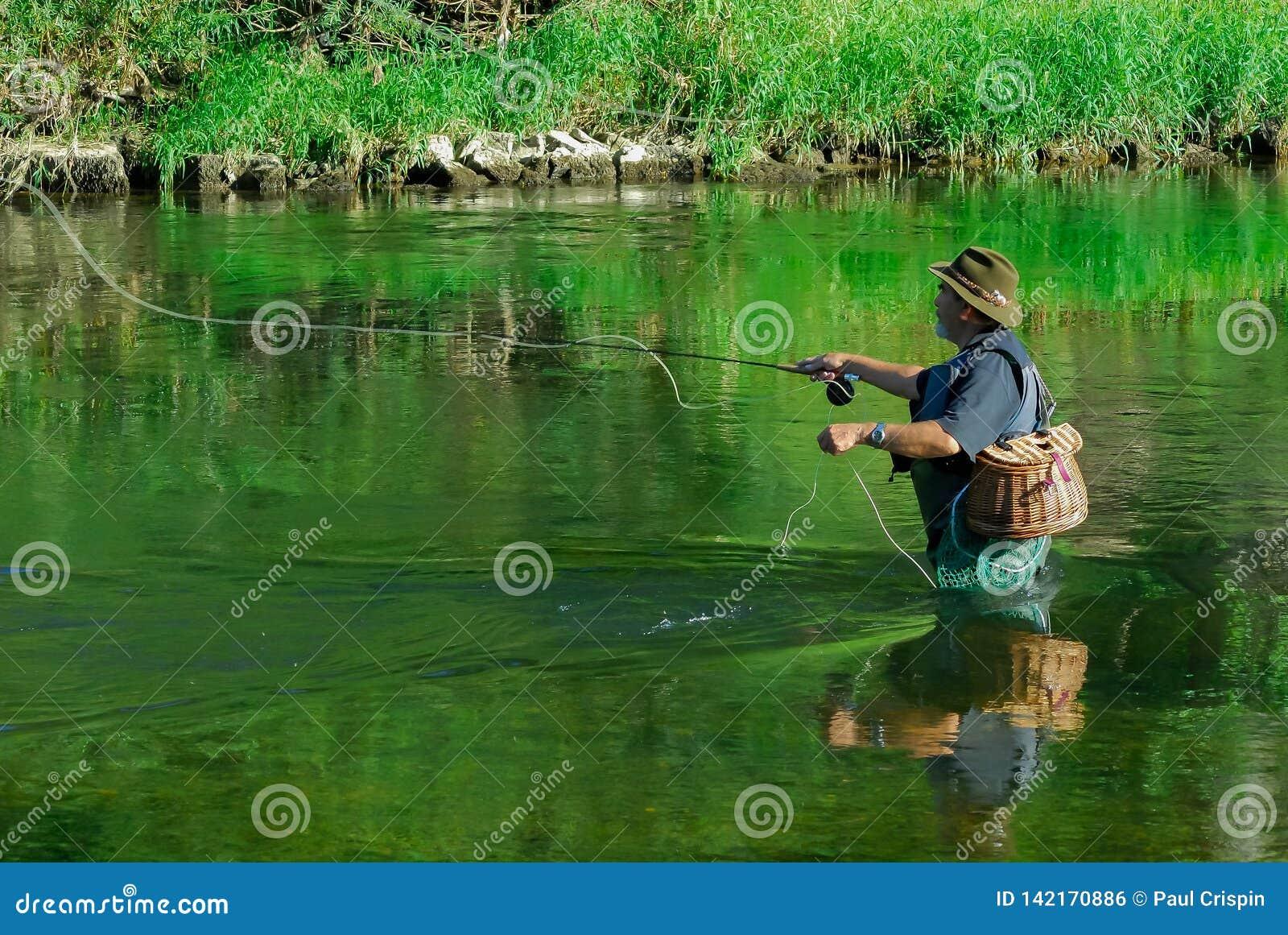 Fliegenfischer im Fluss nach Forelle