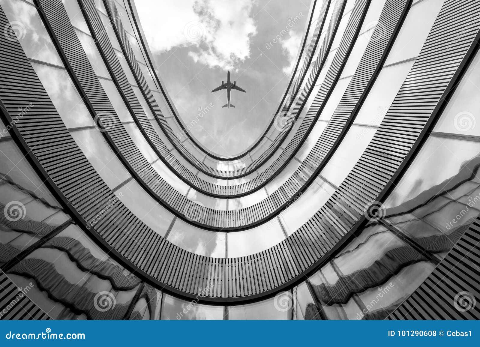 Fliegenflugzeug und modernes Architekturgebäude