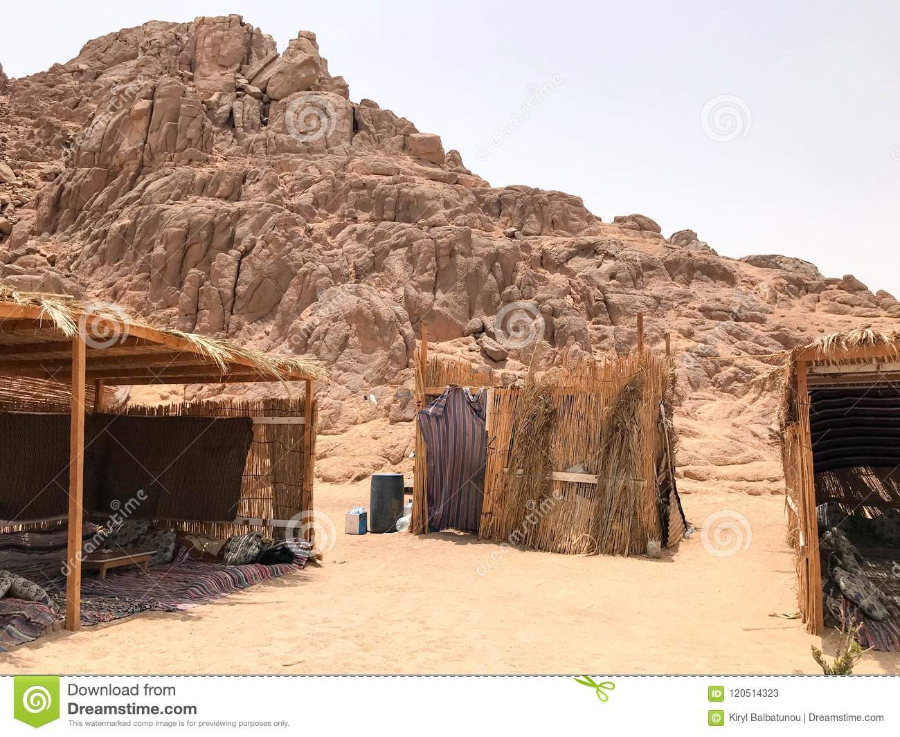 A flimsy, dilapidated decrepit, fragile, fragile poor dwelling, a Bedouin building made of straw, twigs in a sandy hot desert in t
