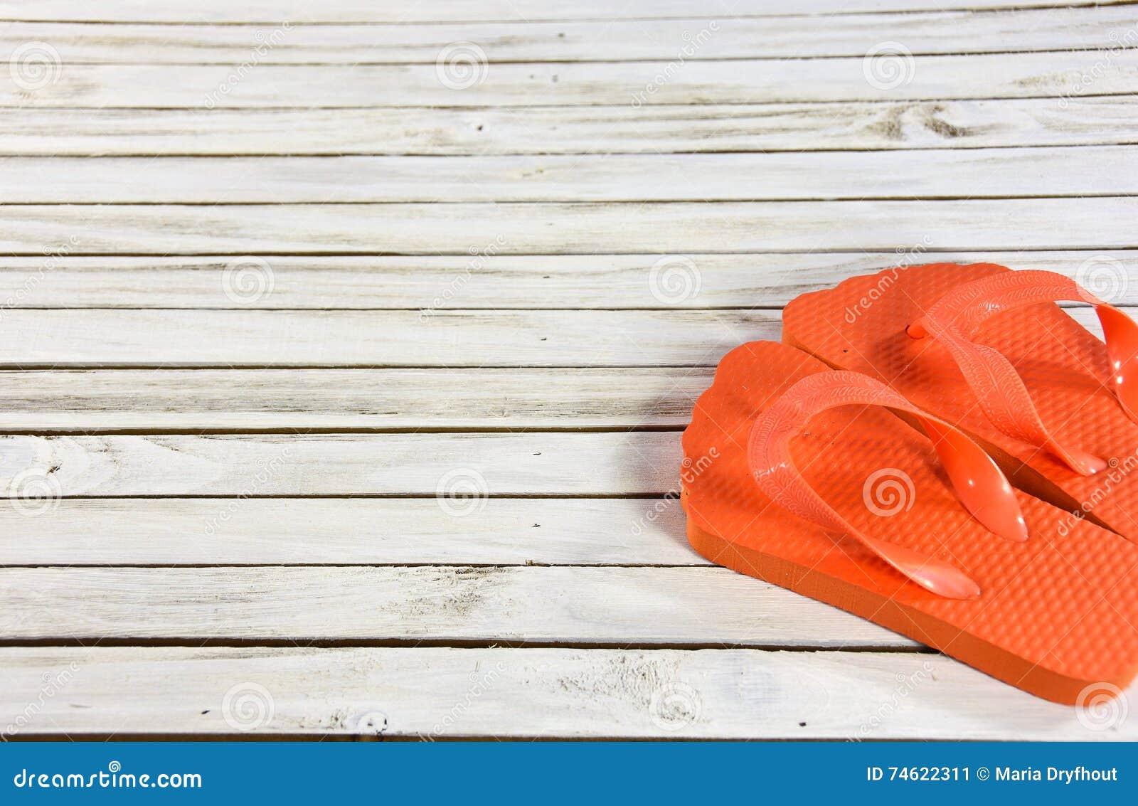 Flip-flop arancio su legno imbiancato
