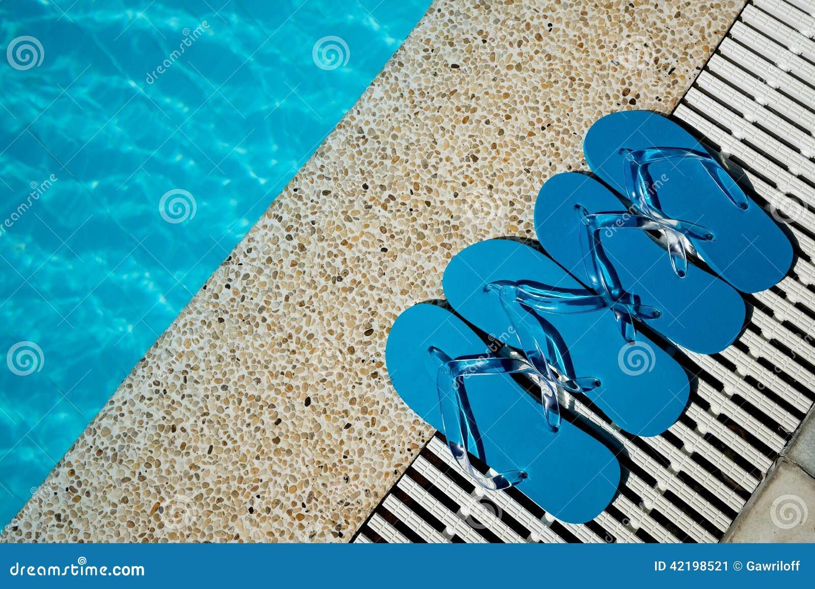 Flip flop en el borde de madera de la piscina del piso con for Piscinas superficie precios