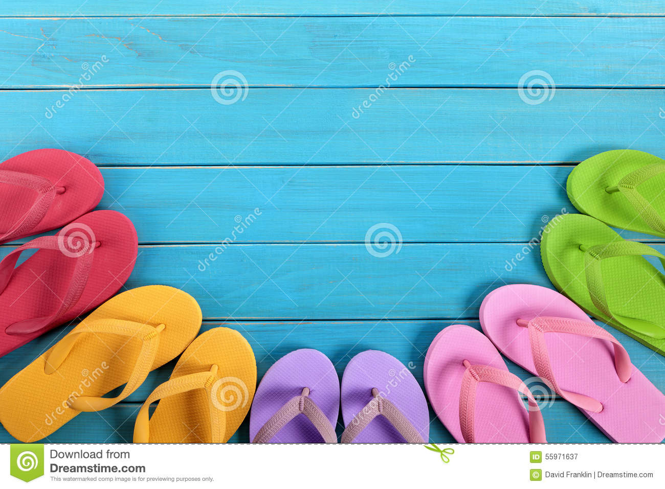 0f4f3c13f96df Semi circle of colorful flip flops on old weathered blue painted beach  decking. Space for copy.