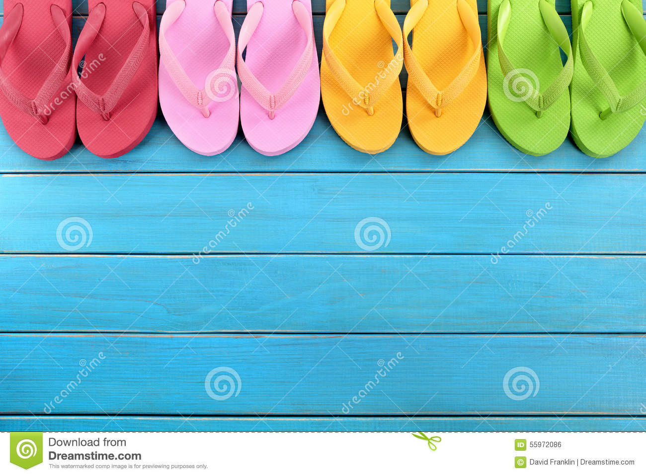 120008f631a4c9 Row of colorful flip flops on old weathered blue painted beach decking.  Space for copy.