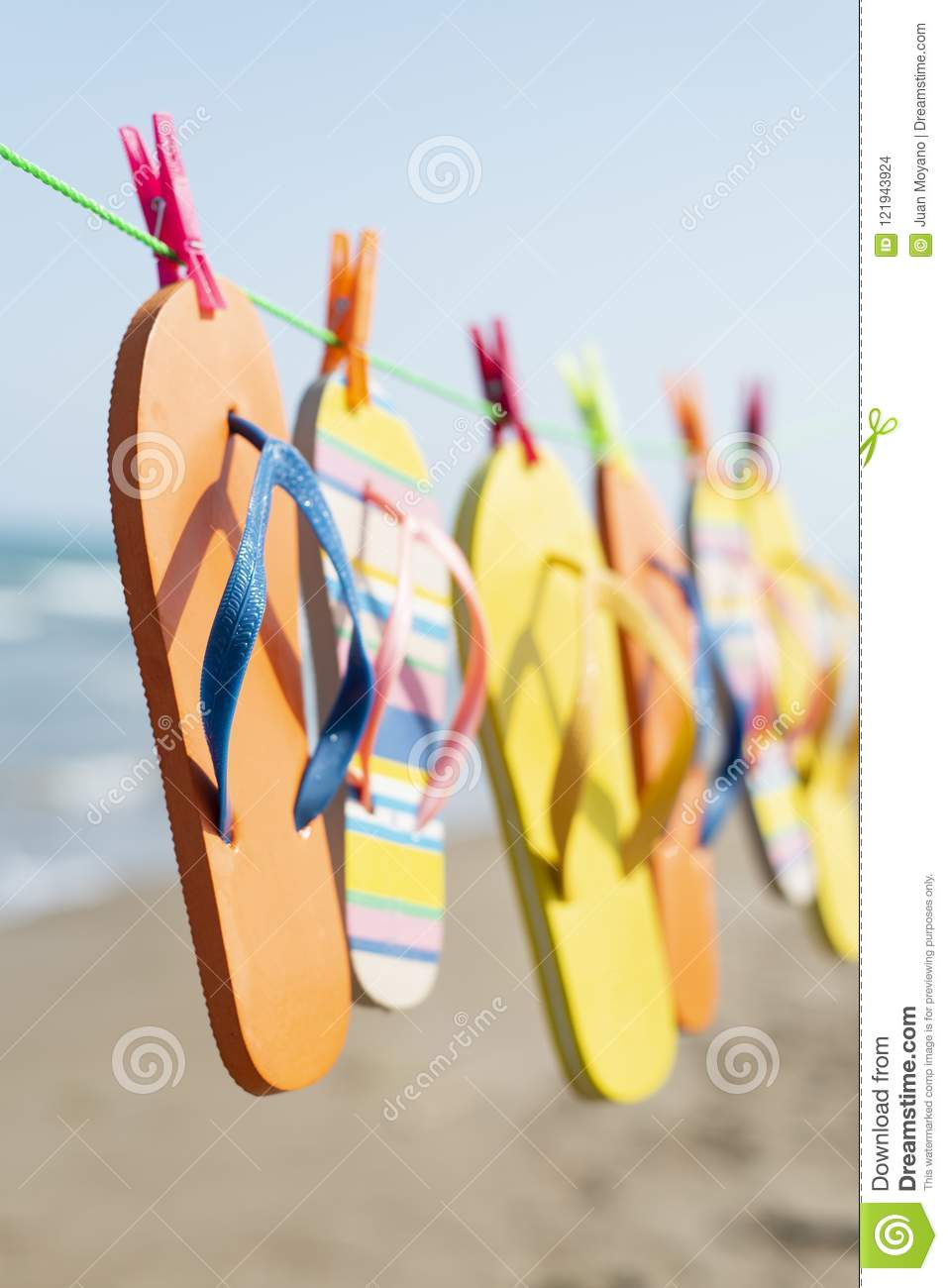 2ffc18c040296d Closeup of some different pairs of colorful flip-flops hanging on a clothes  line on the beach