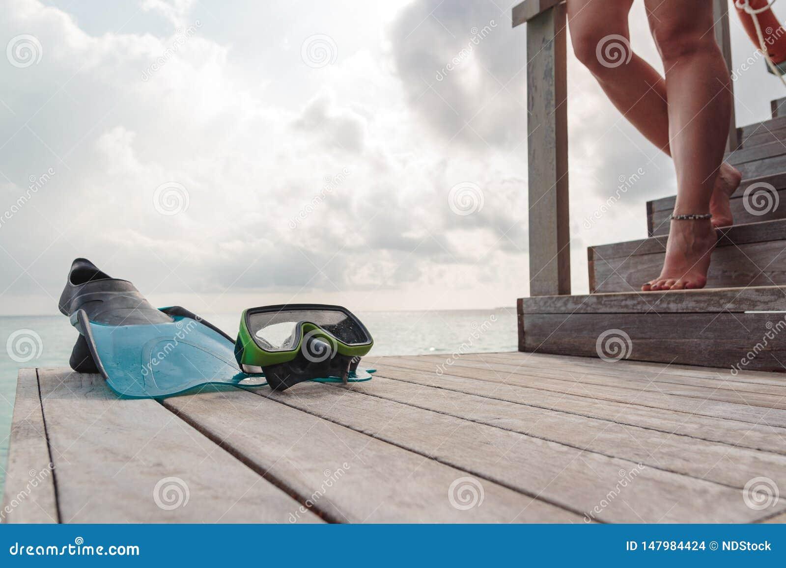 Flipper och maskering på en pir med kvinnaben som stiger ned trappan Molnig himmel som bakgrund
