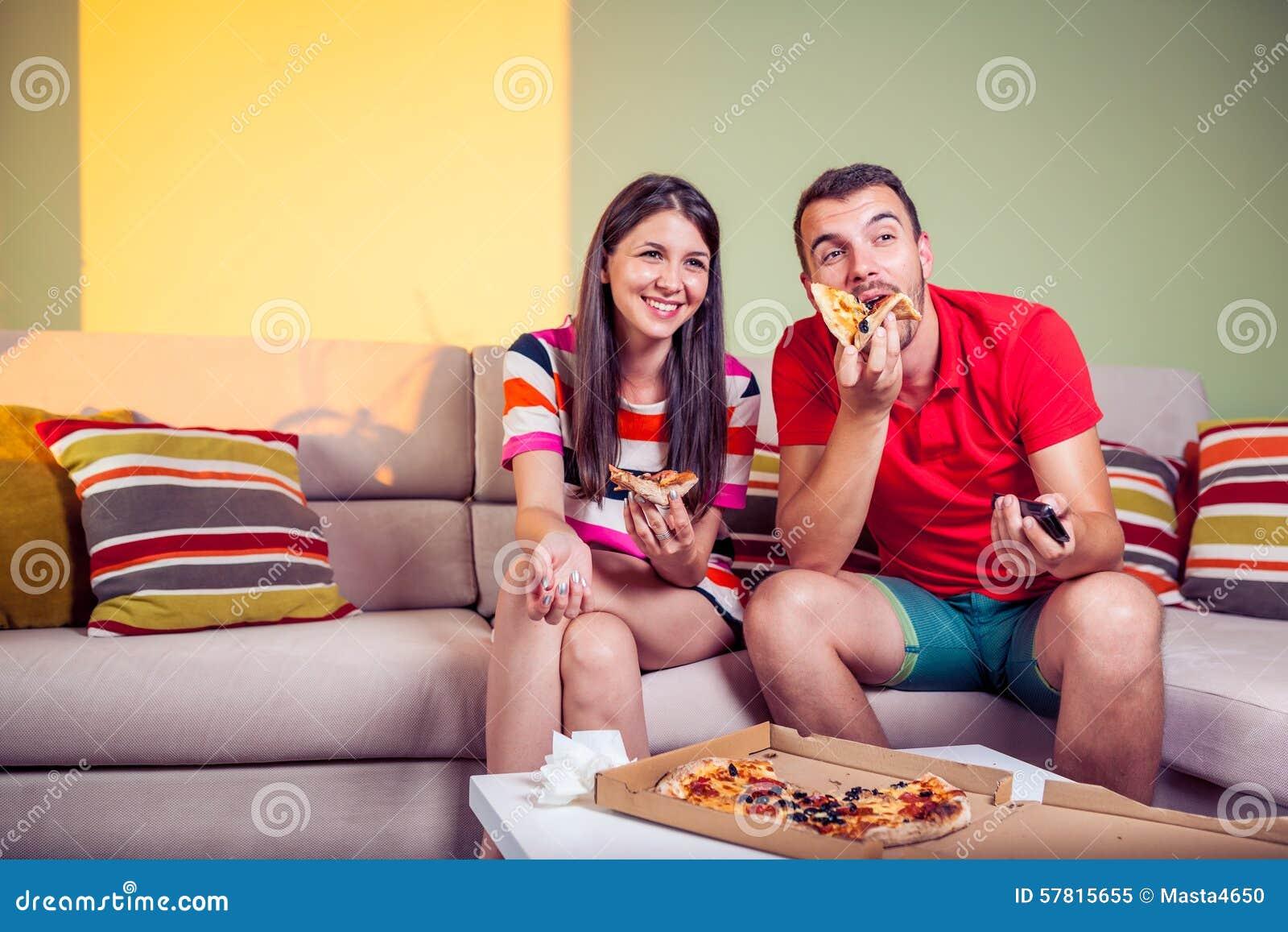Flippige Junge Paare Die Pizza Auf Einer Couch Essen Stockbild