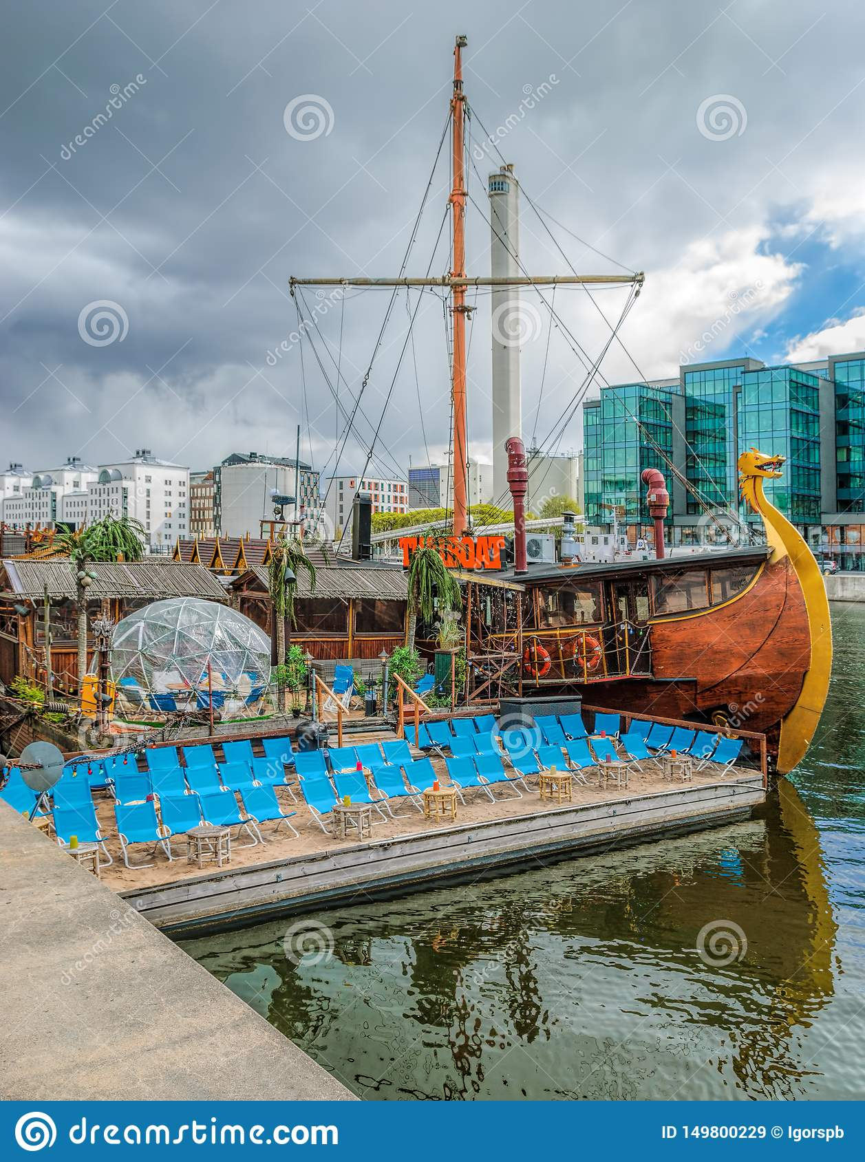 Floating thai restaurant THAIBOAT ih shape of vintage viking ship with own artificial mini beach on a raft on Hammarby canal.