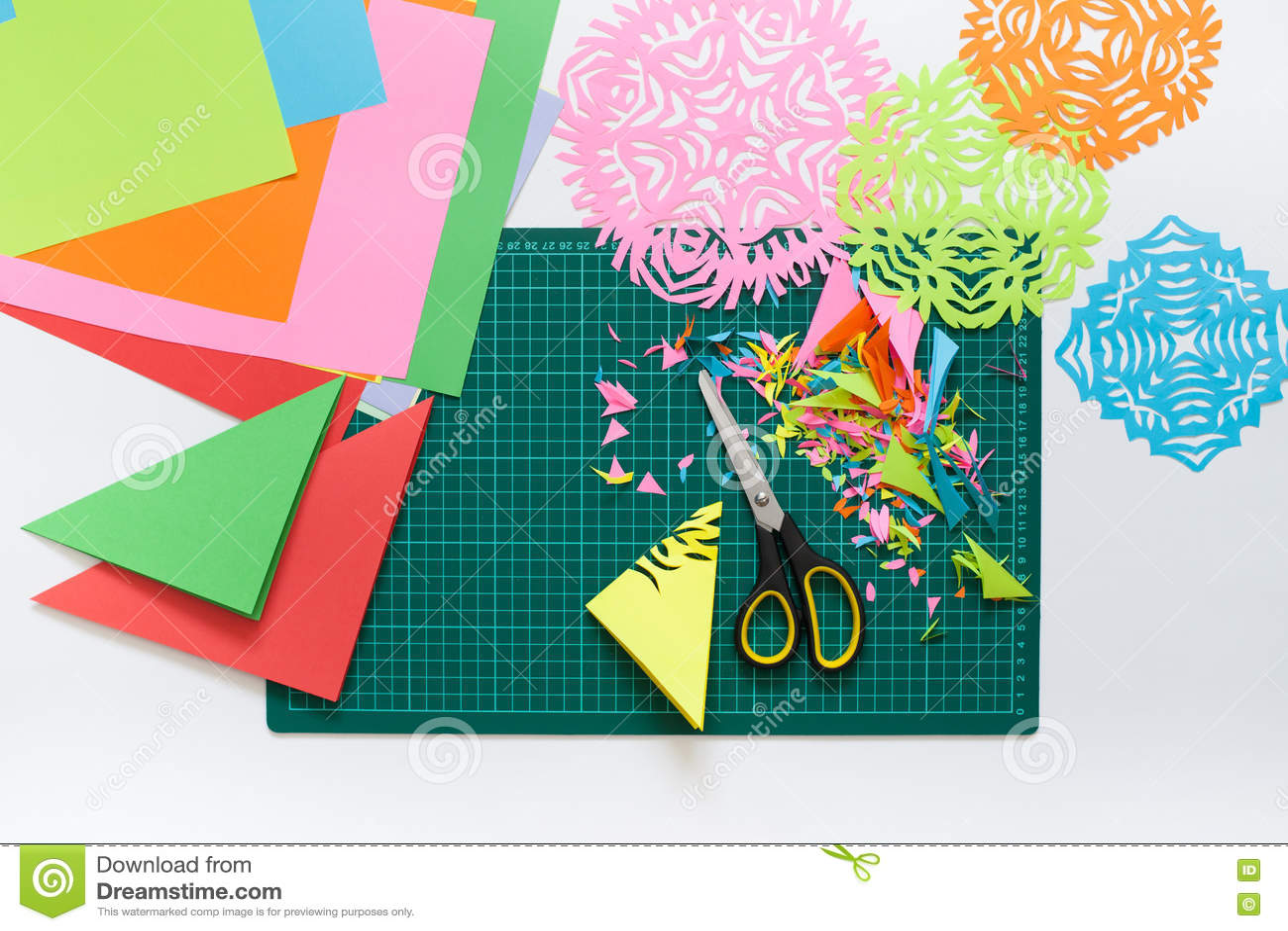 Flocos de neve do papel colorido Tesouras e esteira do corte