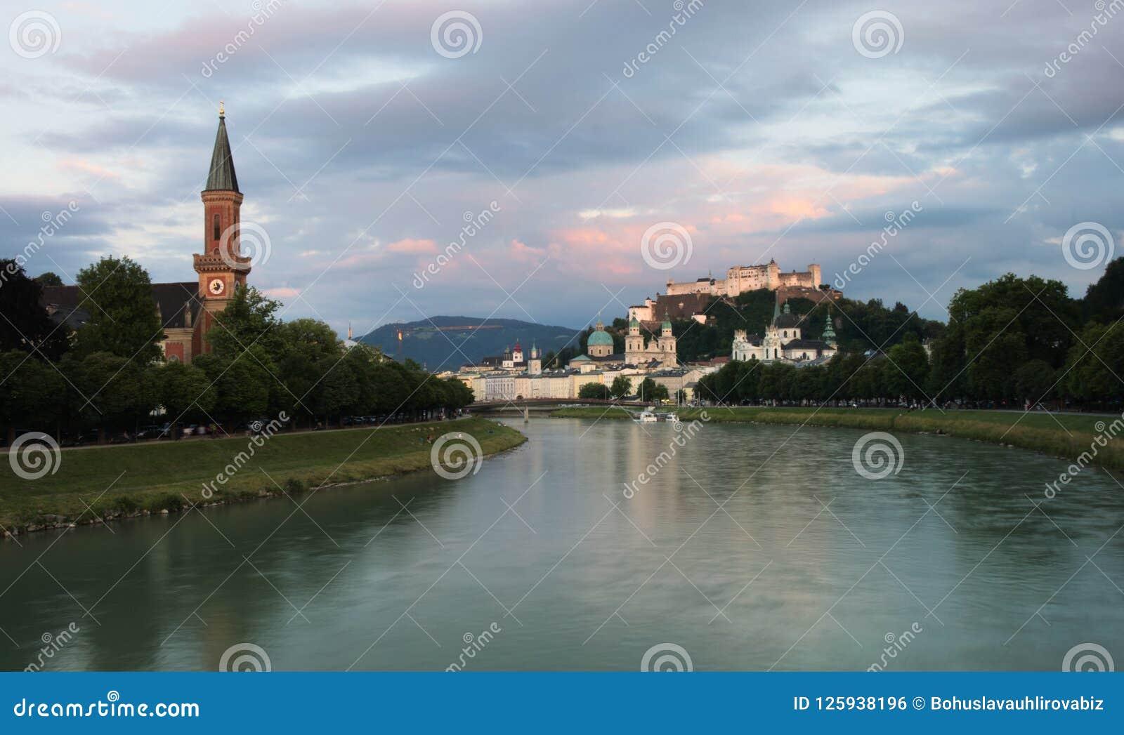 Flod Salzach med Kristuskyrkan Christuskirche på den vänster och Hohensalzburg fästningen på rätten Österrike salzburg