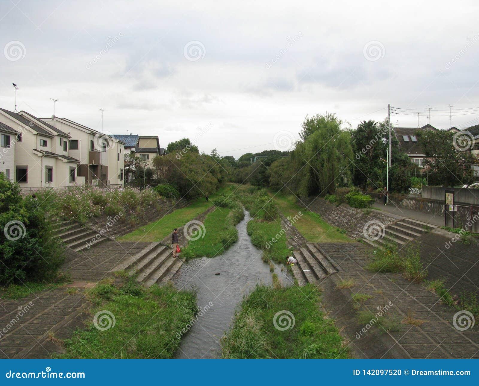 Flod som kör till och med stadsområde i Tokyo, Japan