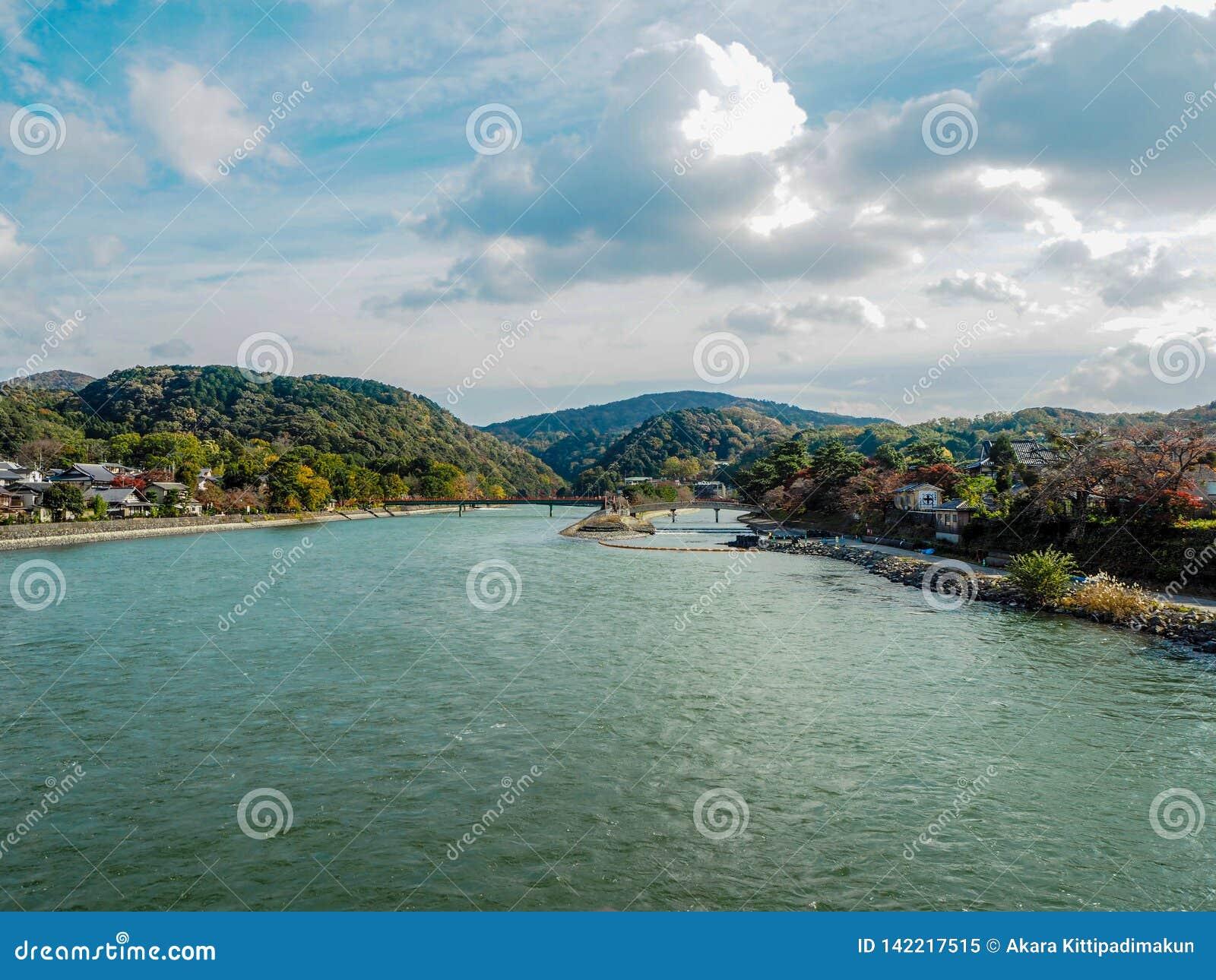 Floden i mitt av en liten stad med berg och bakgrund för molnig himmel