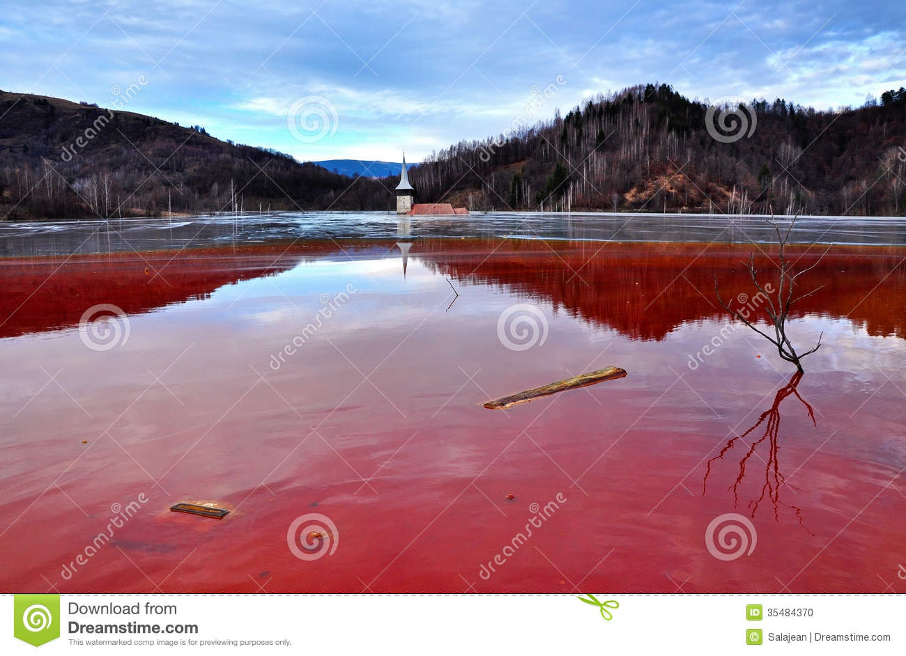 flooded church in a toxic red lake. Water polluting by a copper mine ...