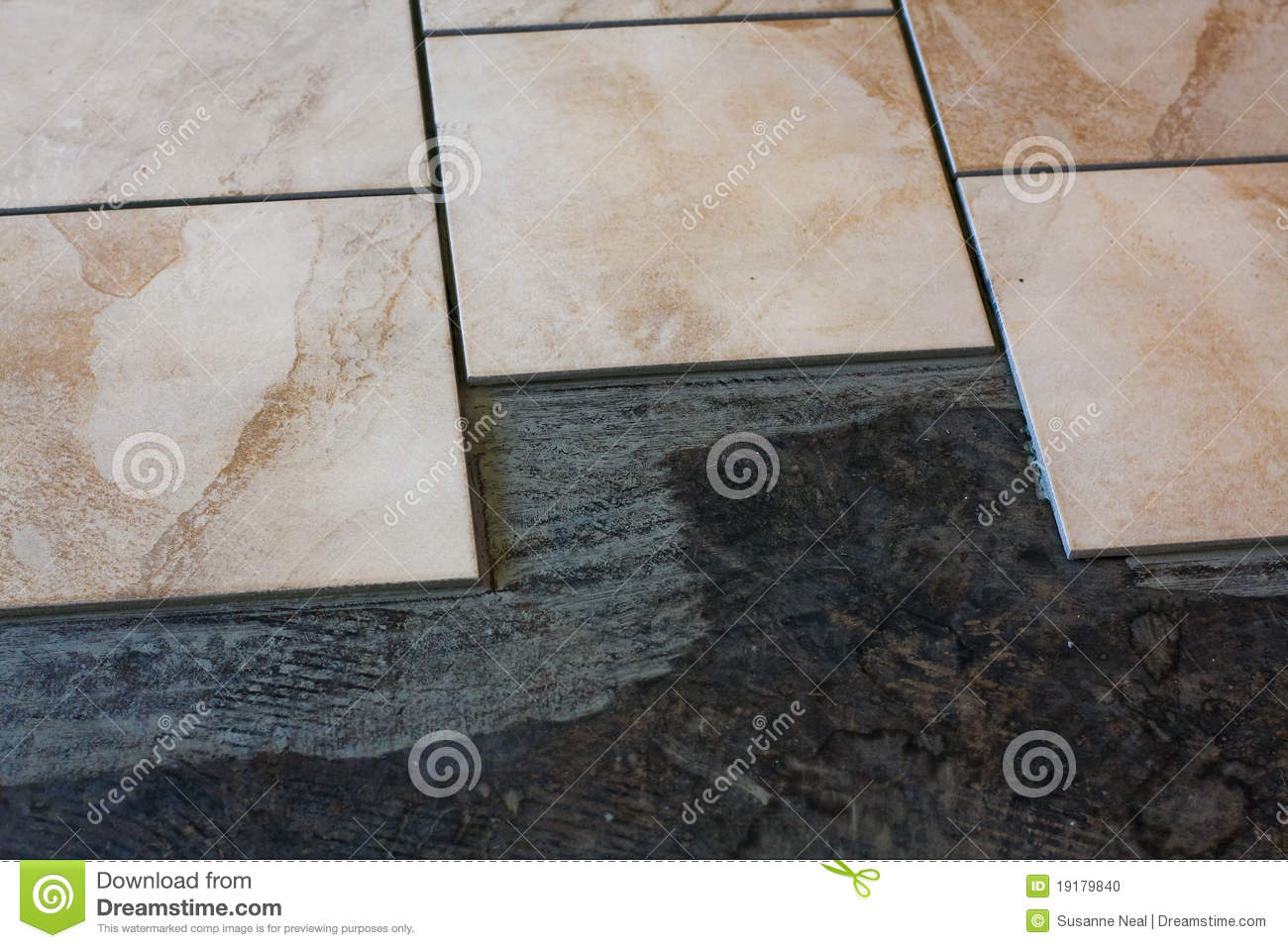 Tan Colored Porcelain Tiles Are Being Installed On A Concrete Floor