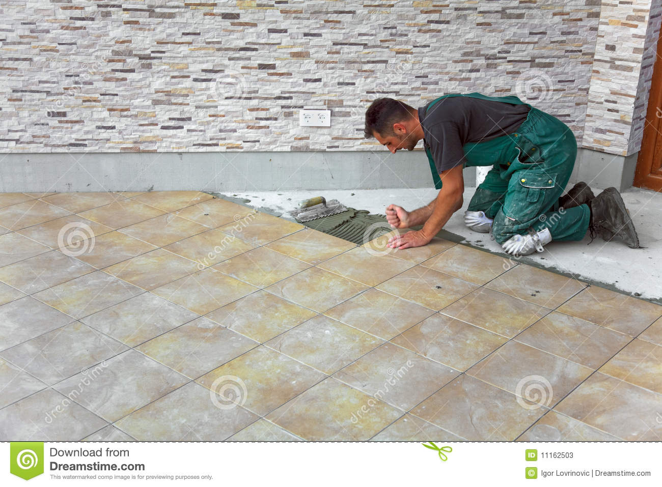 Floor tiles installation stock images 1533 photos floor tiles installation a construction worker putting on new floor tiles stock photos dailygadgetfo Gallery